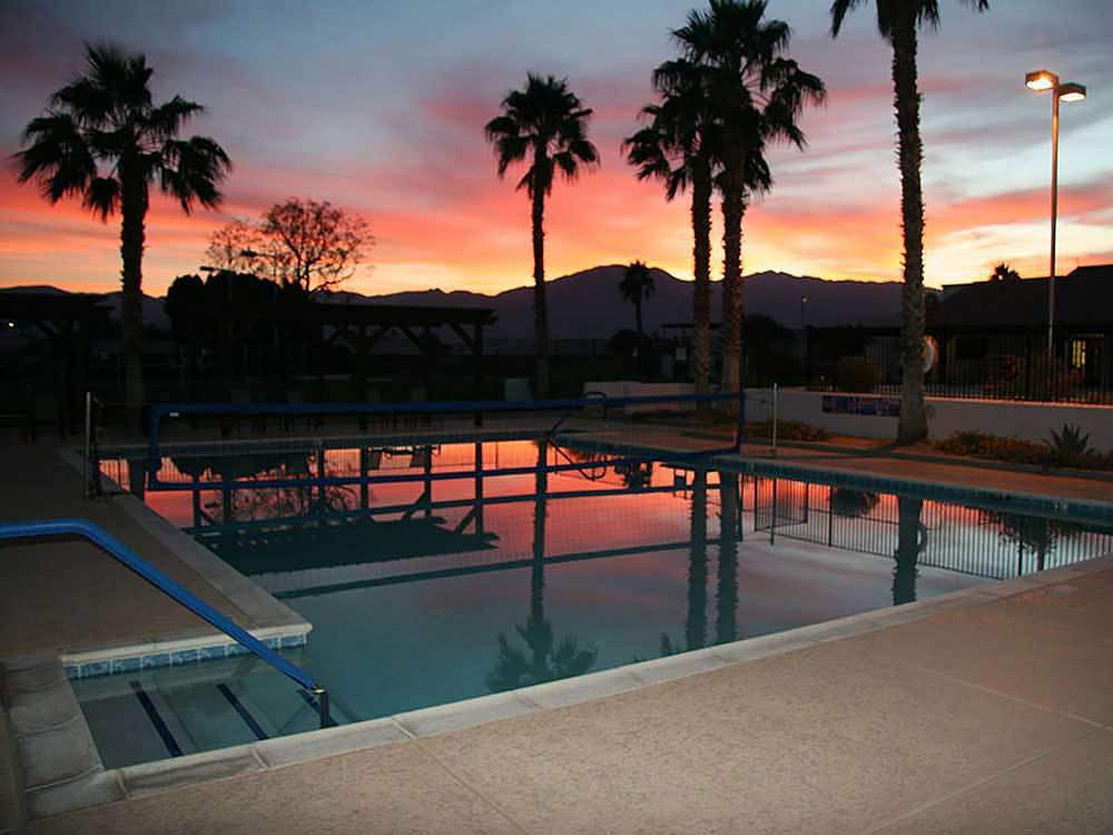 Sun sets behind desert mountains as a placid pool reflects the red light in the shadows of palm trees.