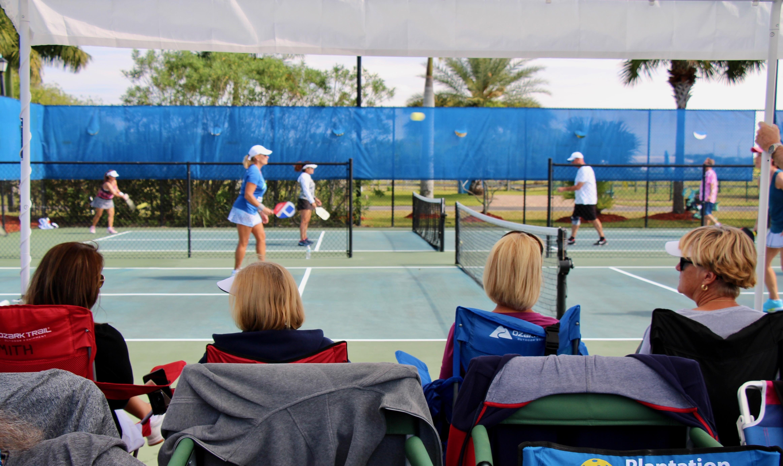 Spectators watch a pickleball match.