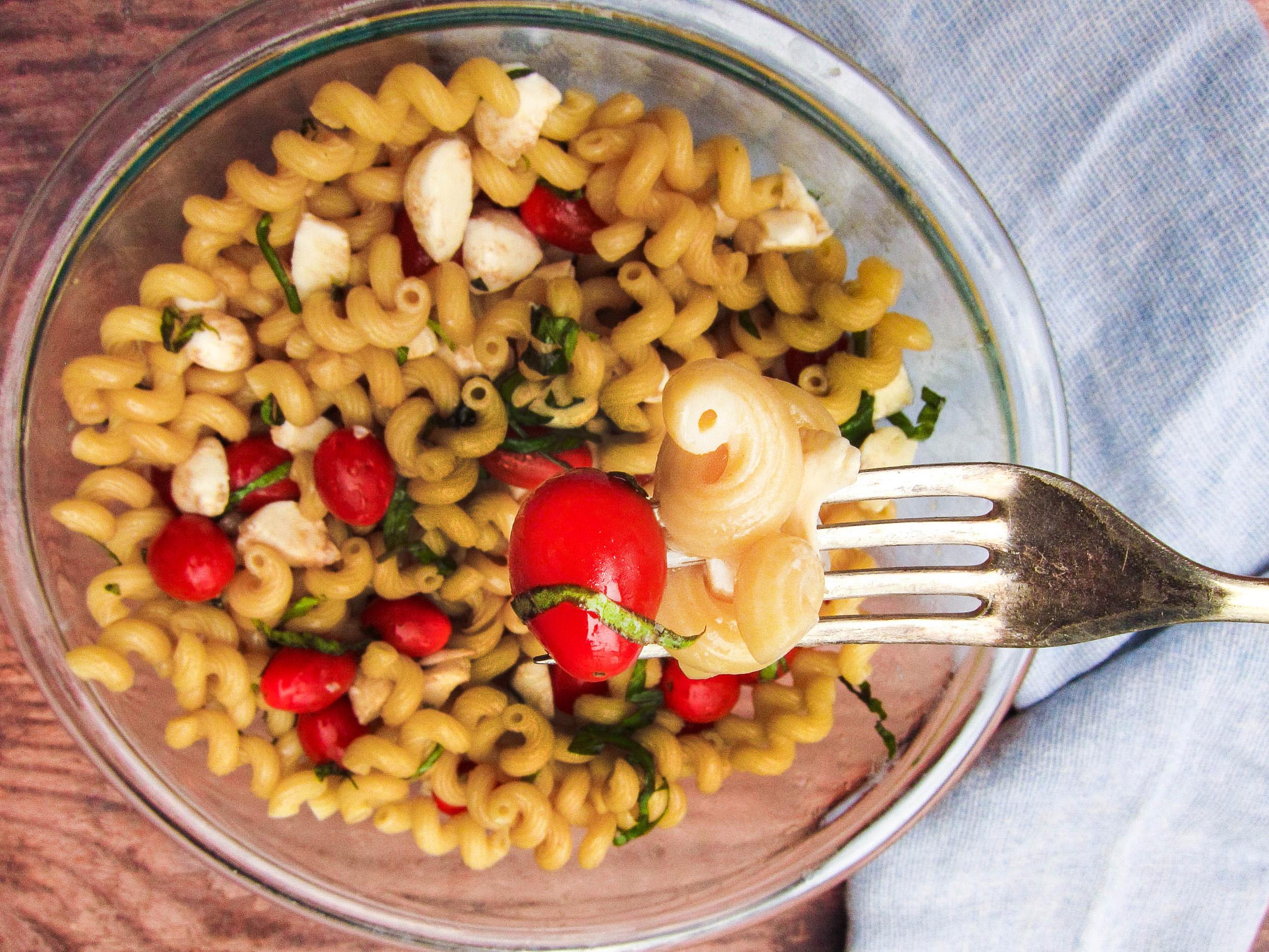 Fork stabbing into pasta salad.