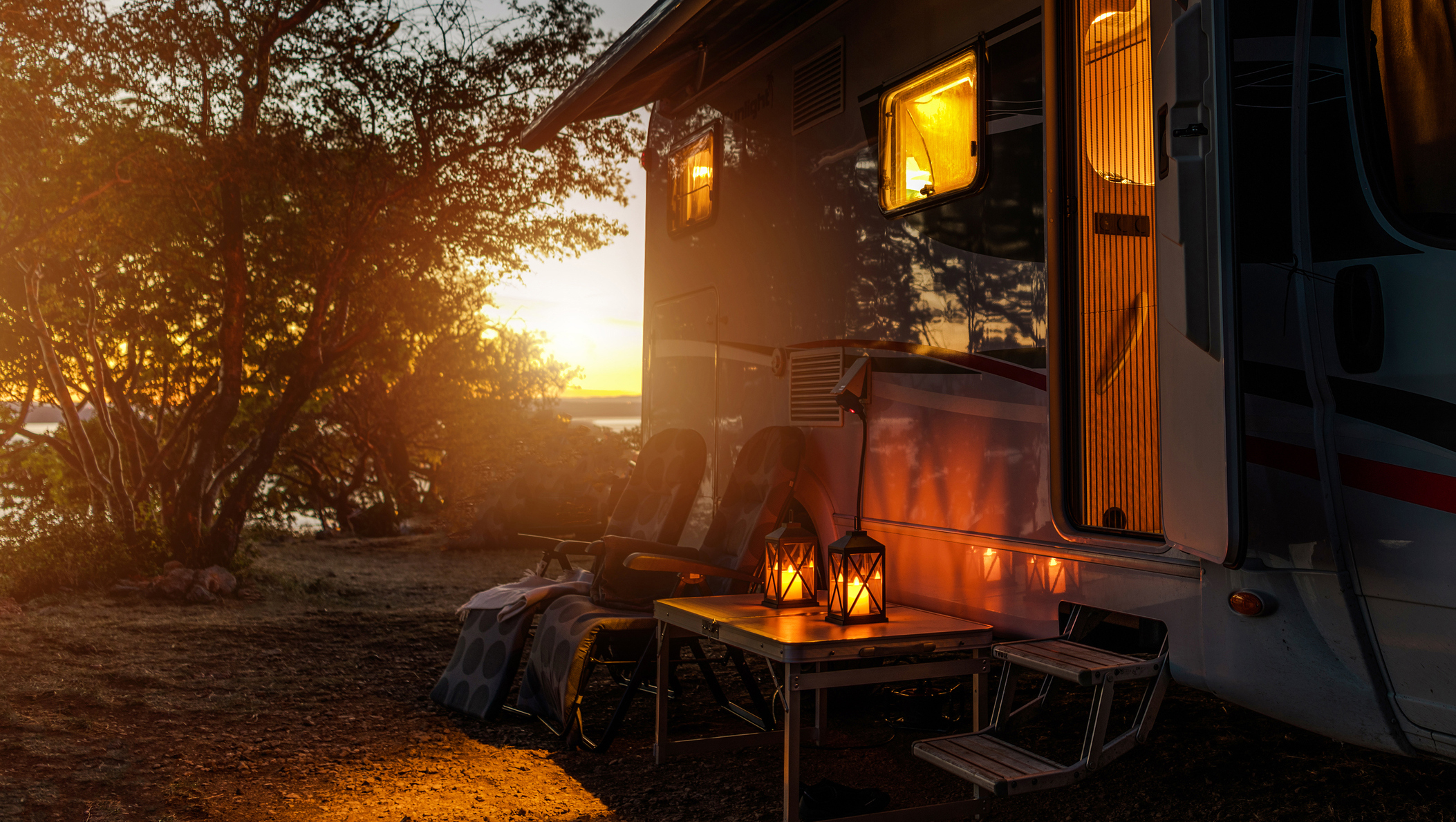Practice good manners —An RV casts a welcoming glow onto a dusk campsite.