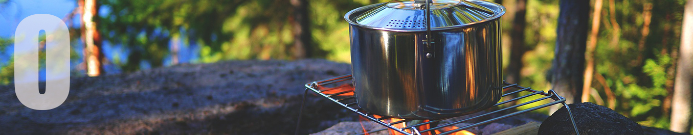A pot sits on a grill over a campfire in a wooded area.