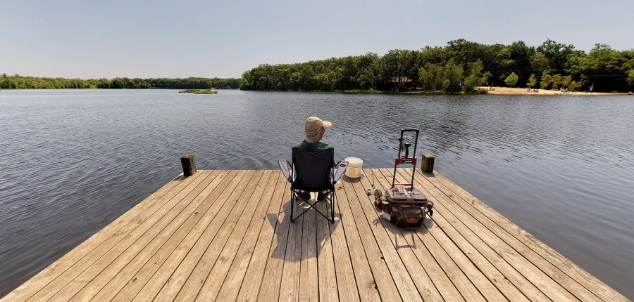 something for everyone in the family — a man fishing on a dock overlooking a beautiful lake.