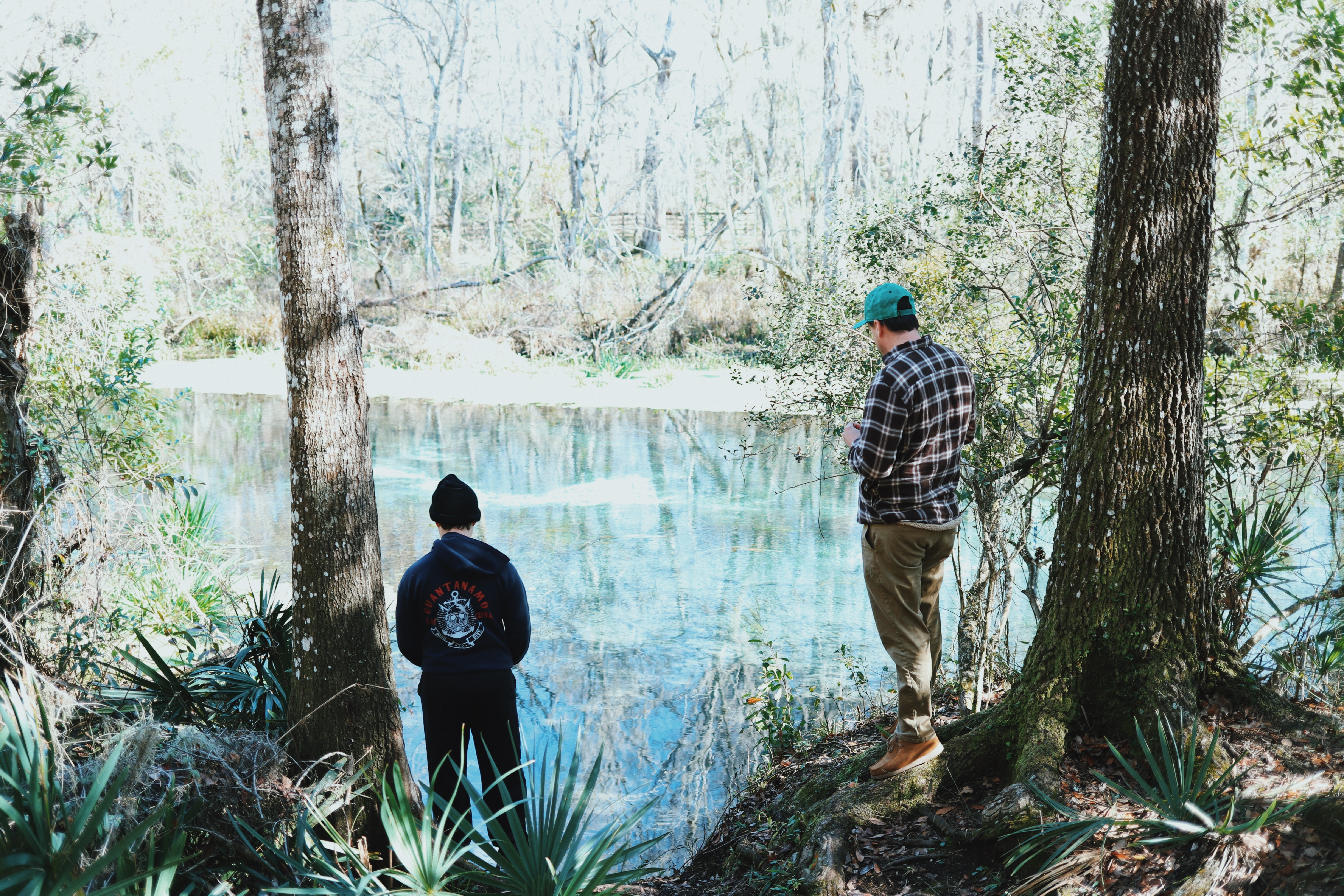 Two men fishing on the banks of a clear river.