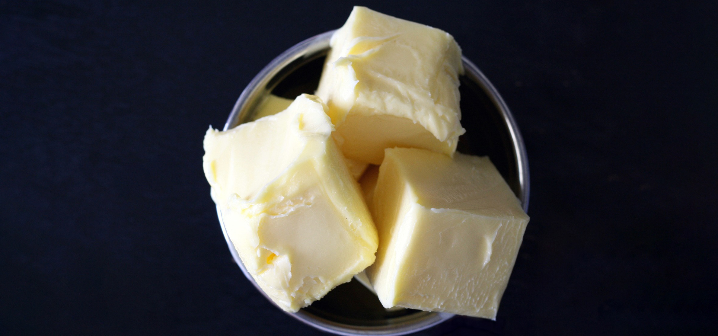 Cubes of butter against black background.