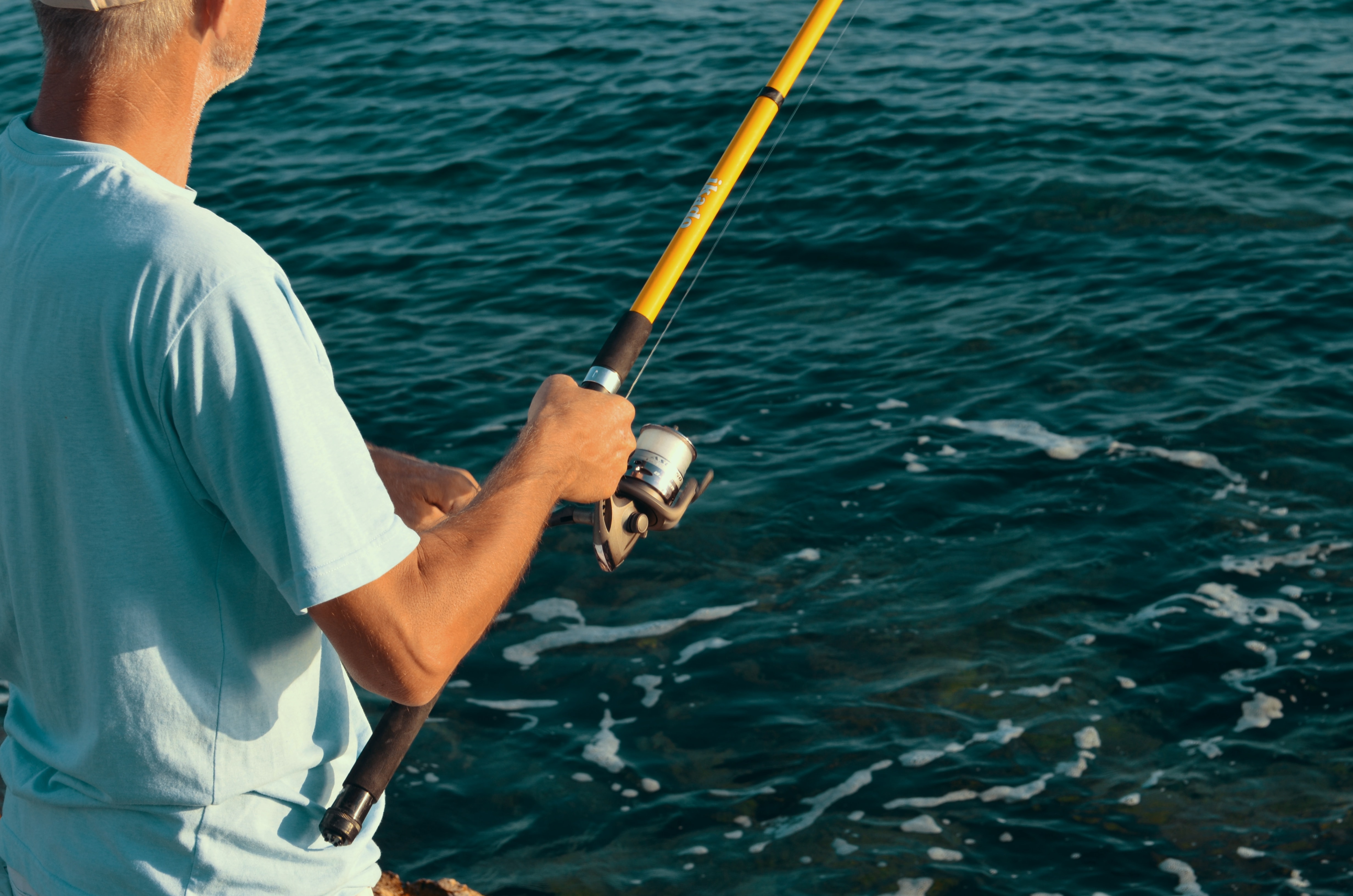 Man fishing with yellow pole in dark blue waters.