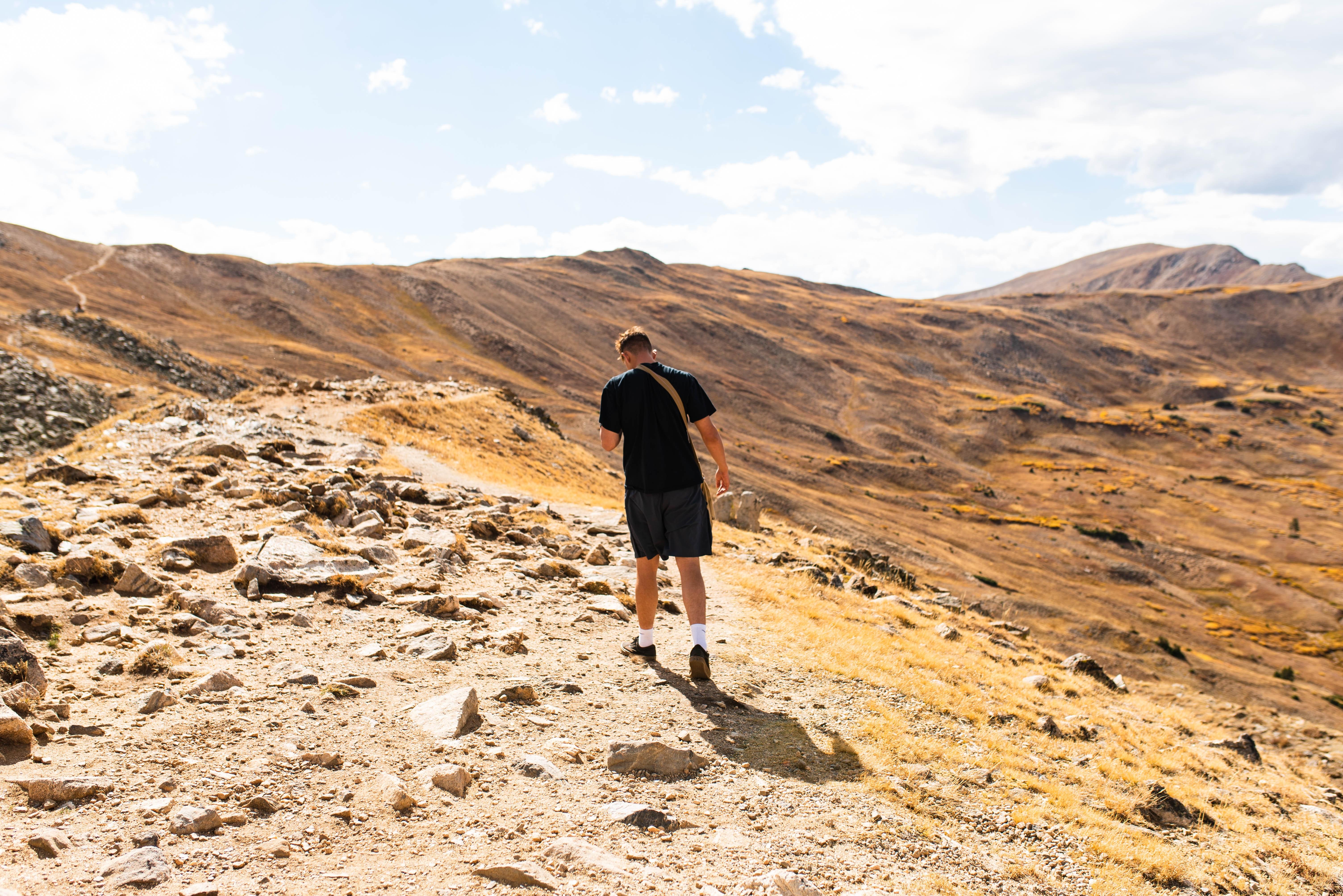 A lone hiker follows a trail that runs atop a ridgeline.