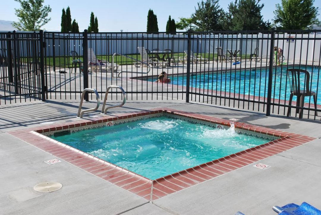 Square hot tube with pool beyond a fence separating the two.
