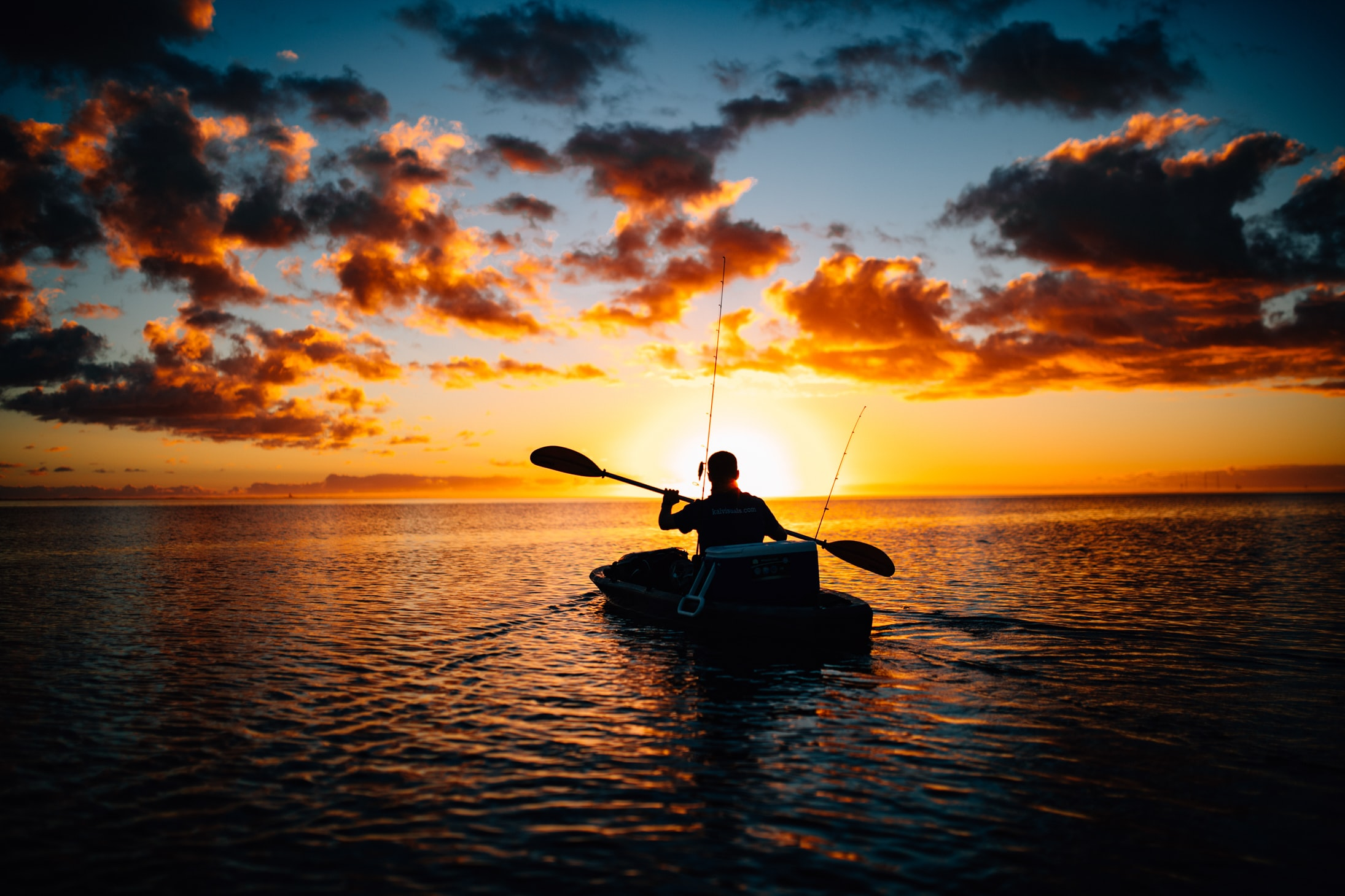A man kayaks toward a beautiful red sunset.