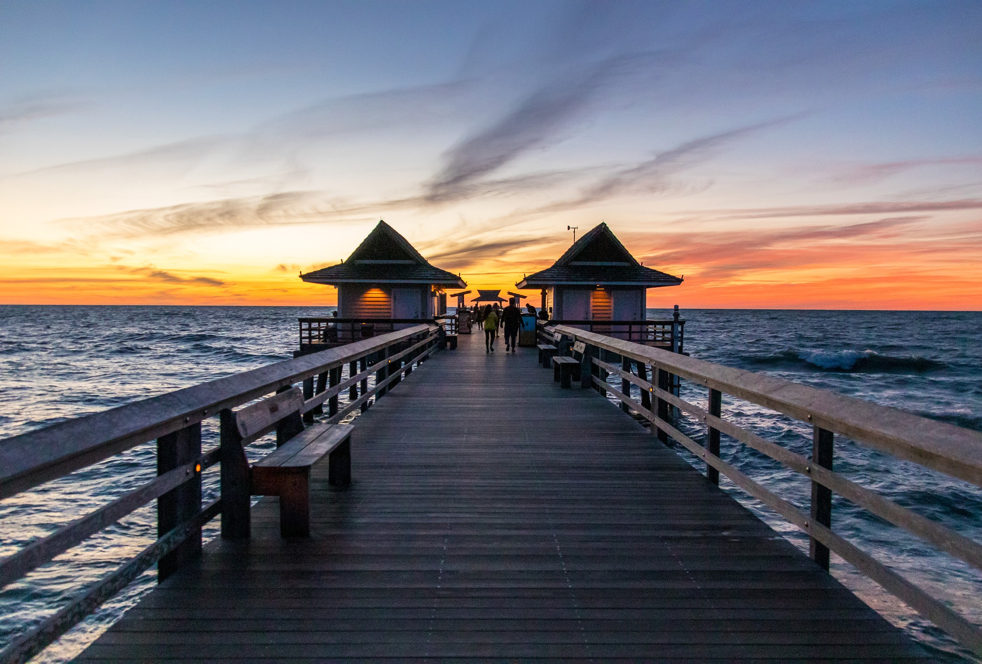 A pier stretching into the ocean toward sunset.
