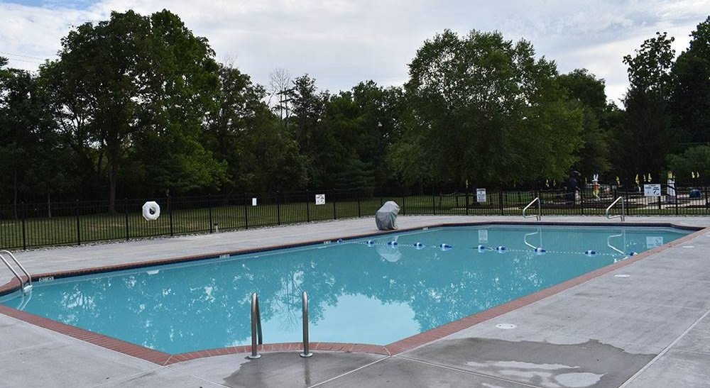 A swimming pool surrounded by black fence.