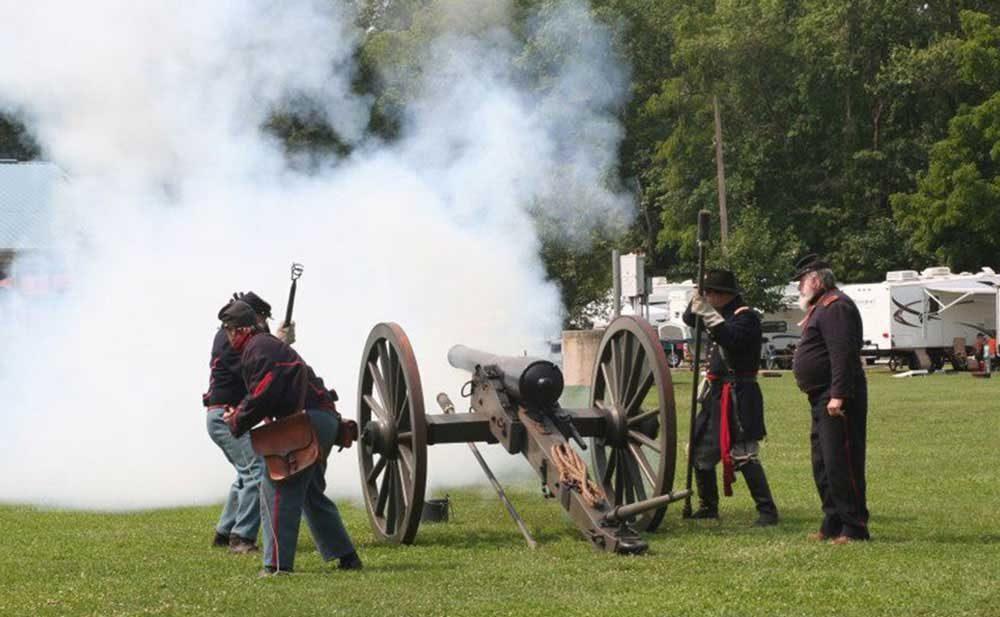 Civil war re-enactors fire a cannon in an RV park.