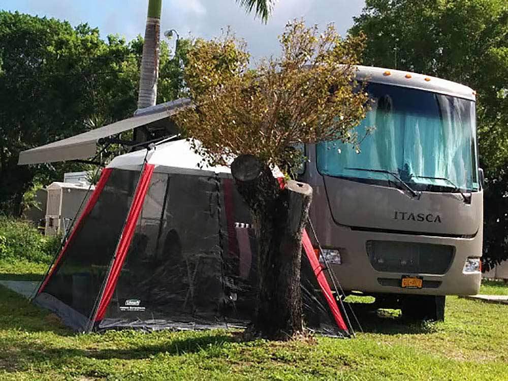 An RV next to a tent.