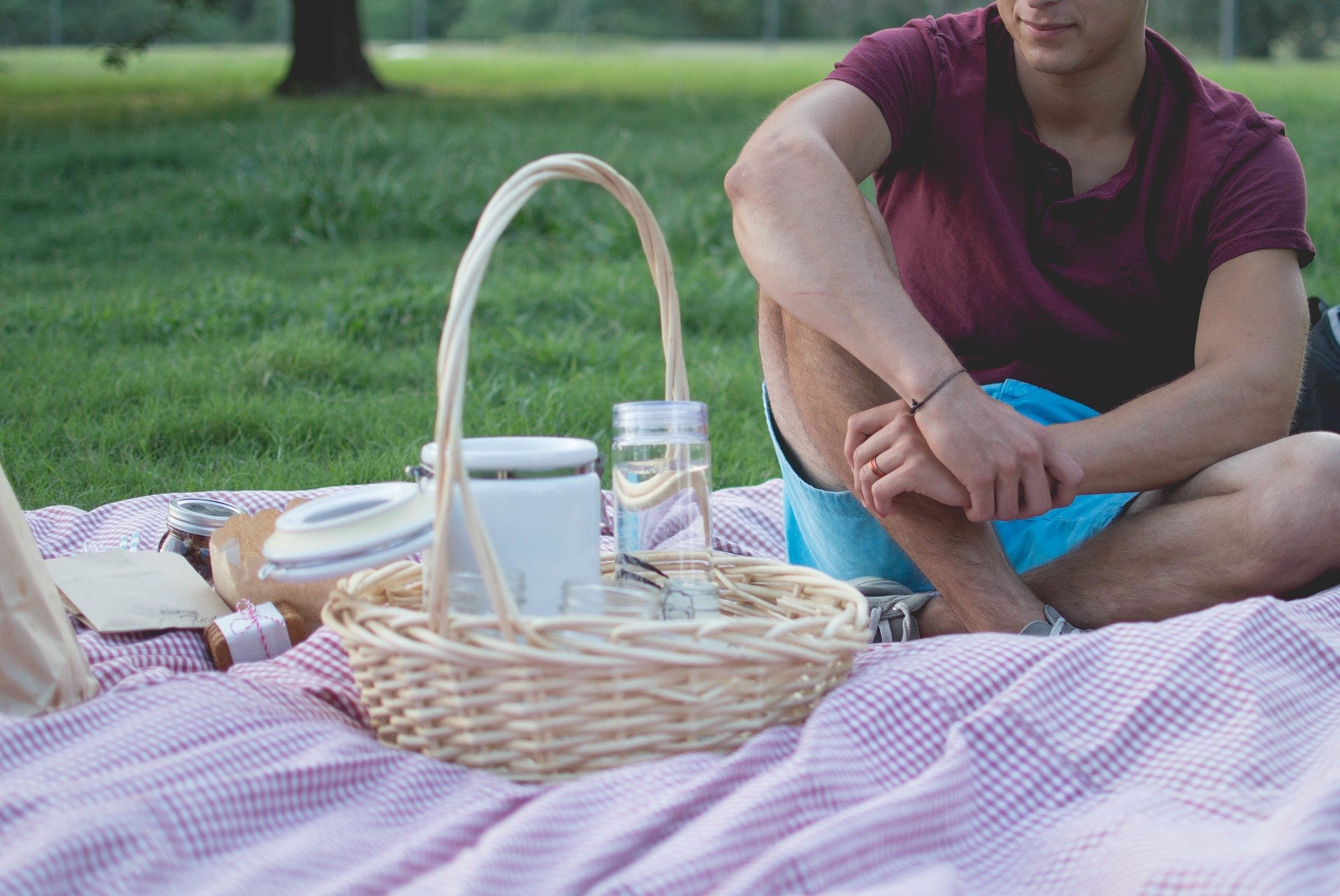 Man in blue shorts sits on picnic blanket and gazes on basket of glasses and food.
