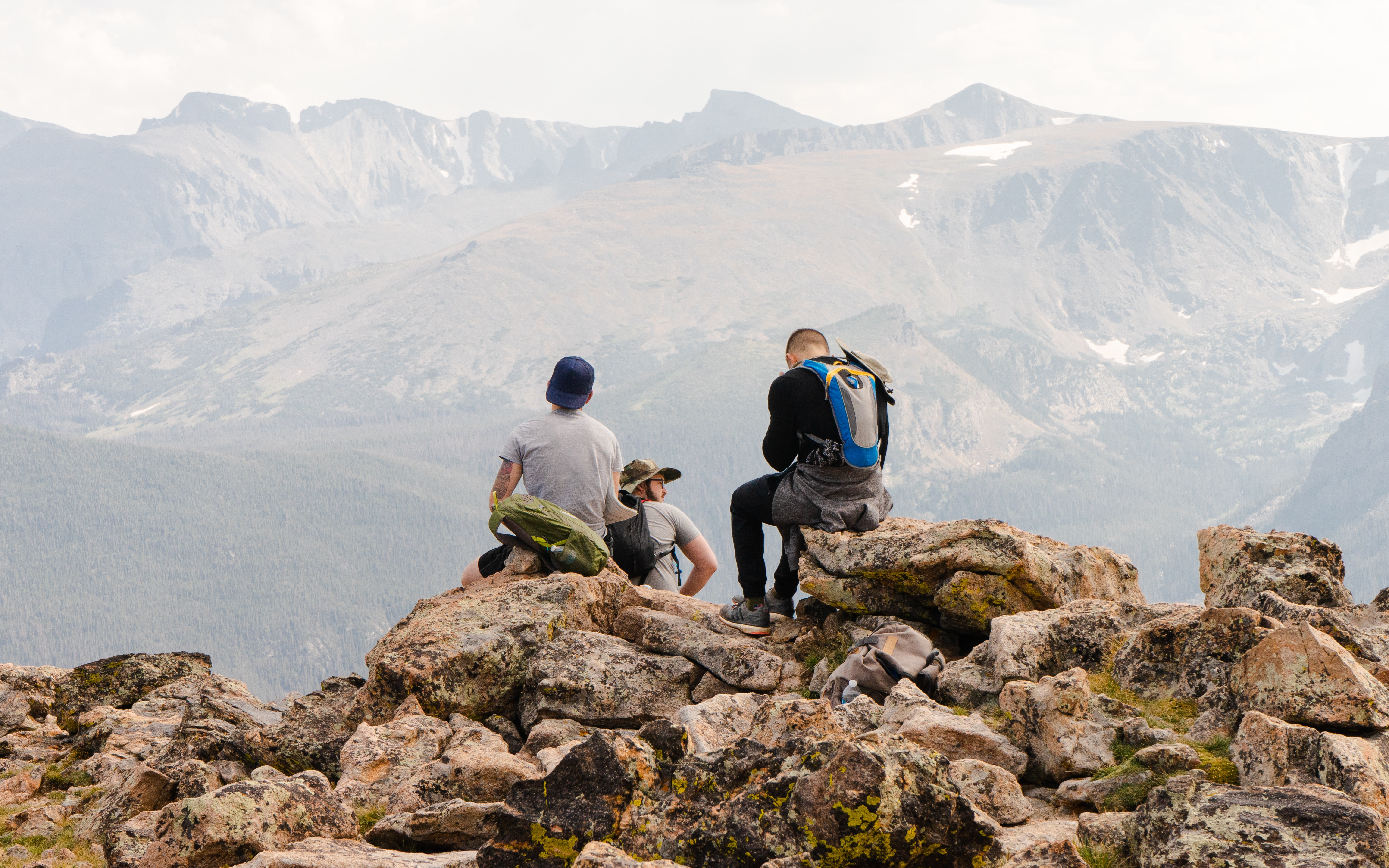 Three hikers relaxing on a mountaintop.