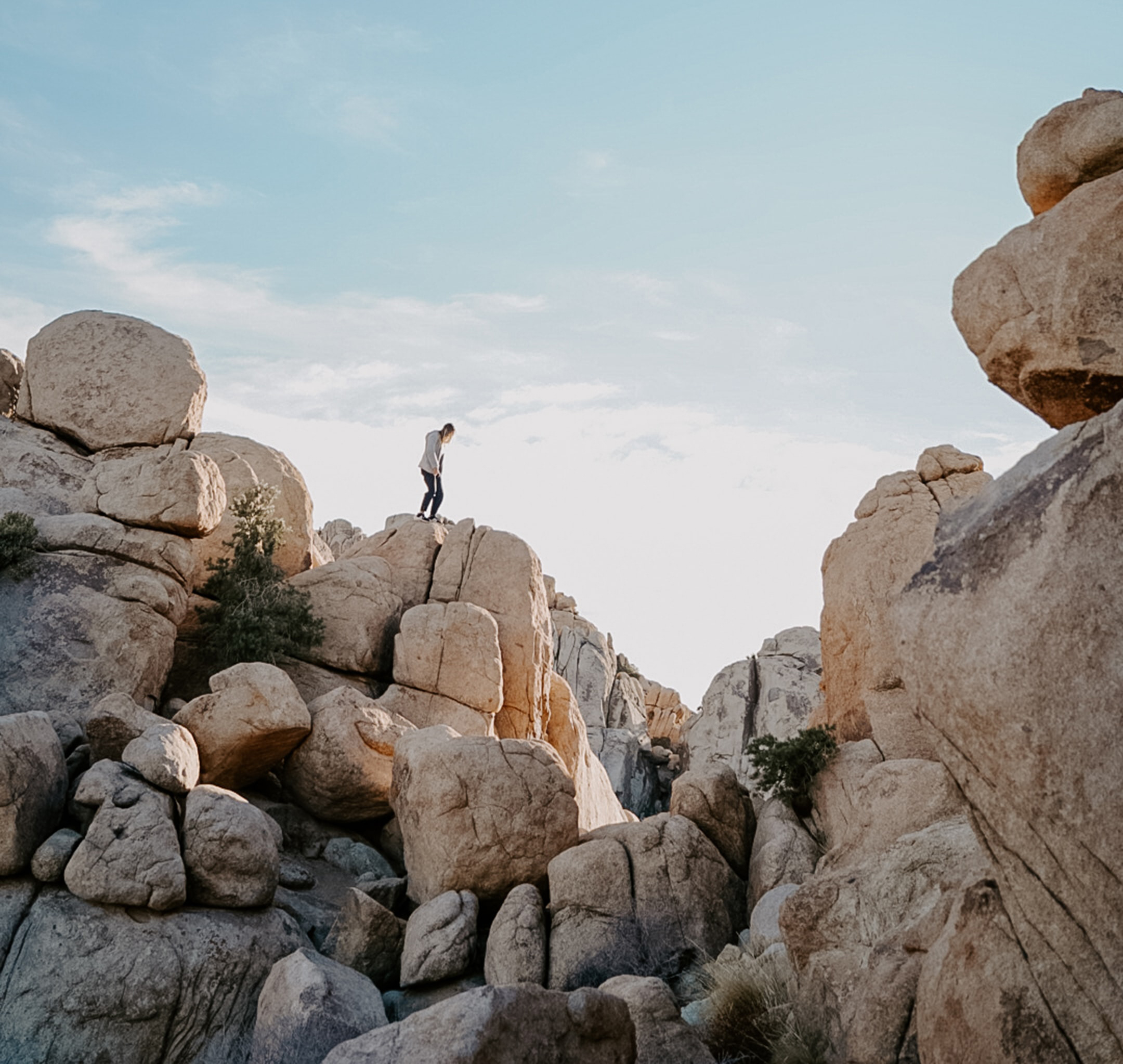 A lone hiker traverses desert boulders.