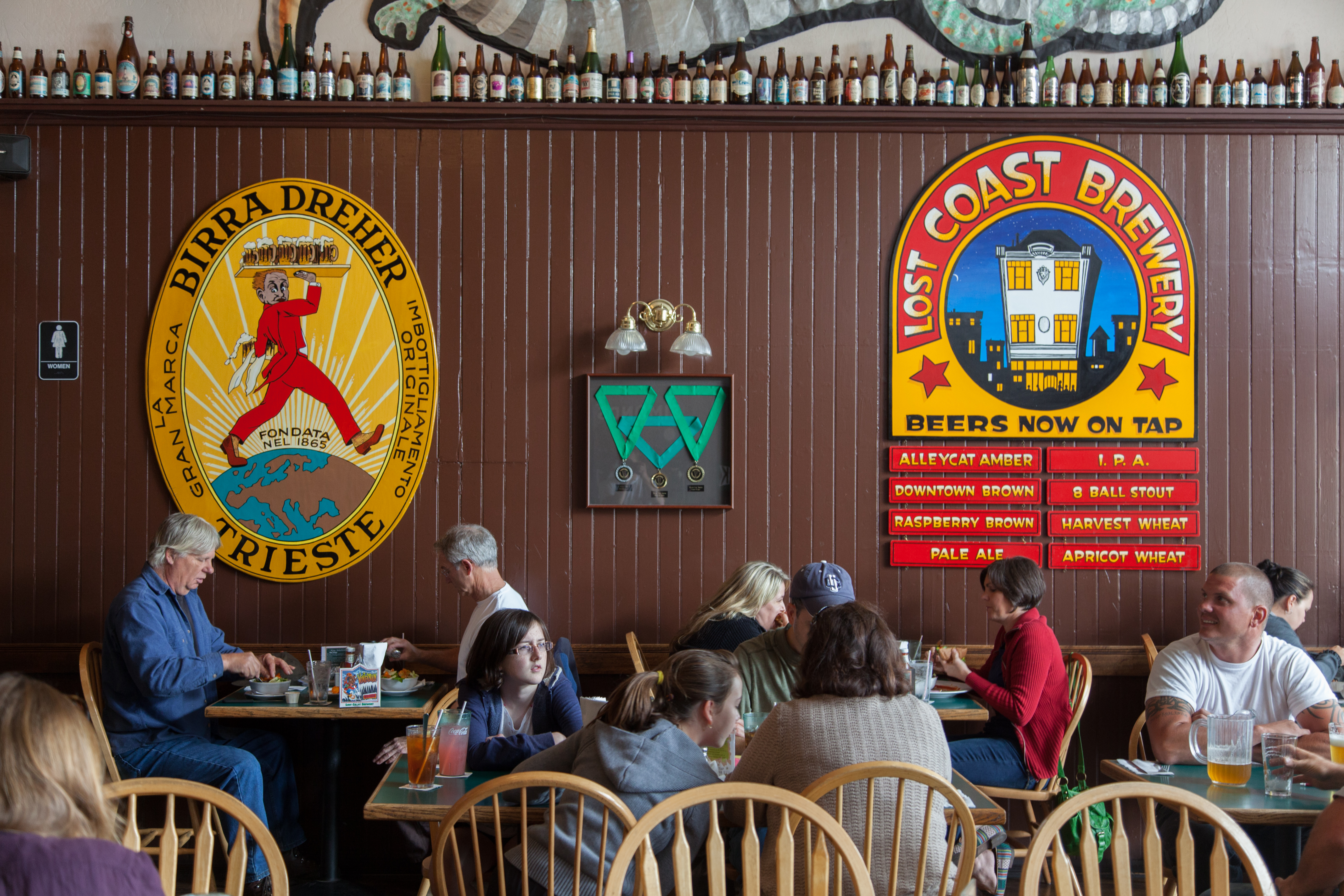 """Western Craft Beer Destinations — Customers sit at tables under signs that proclaim, """"Lost Coast Brewery."""""""