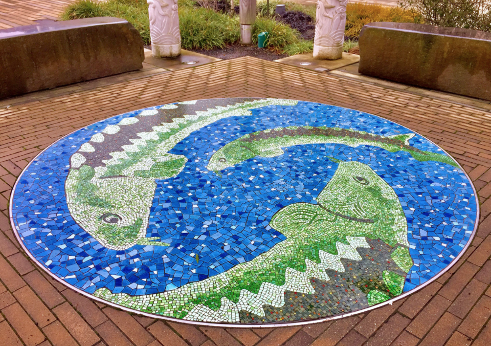 A mosaic of fish on a brick patio.