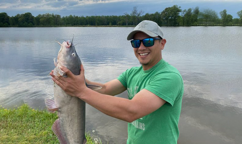An angler proudly shows off a hefty catfish on the shores of a lake.