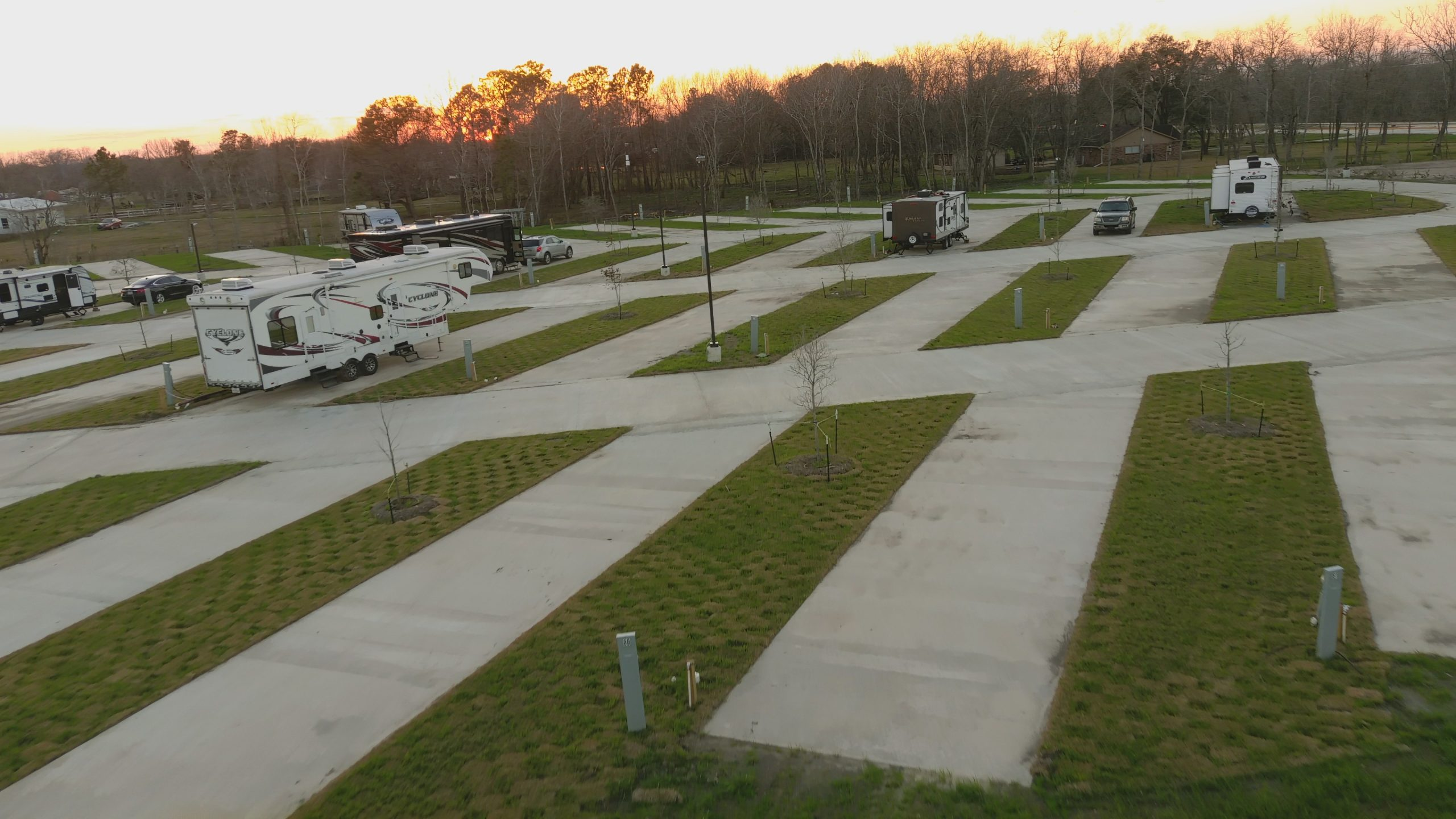 RVs on paved spaces in a clearing surrounded by forest.