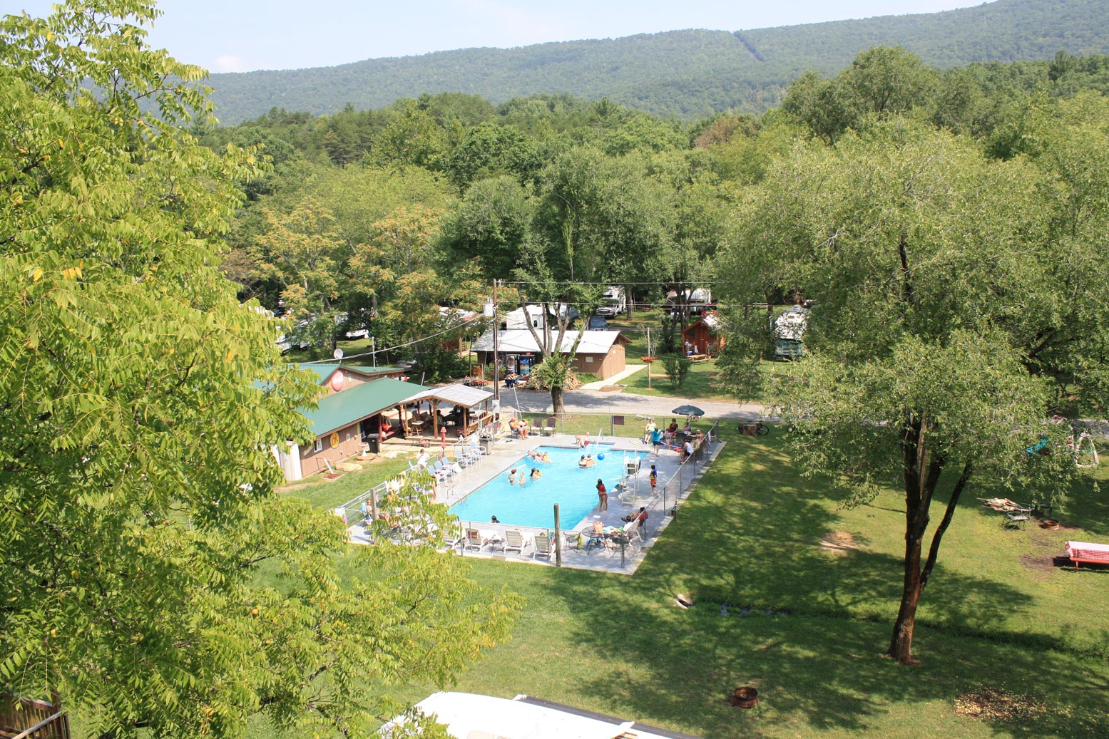 An RV park pool surrounded by lush green forest.