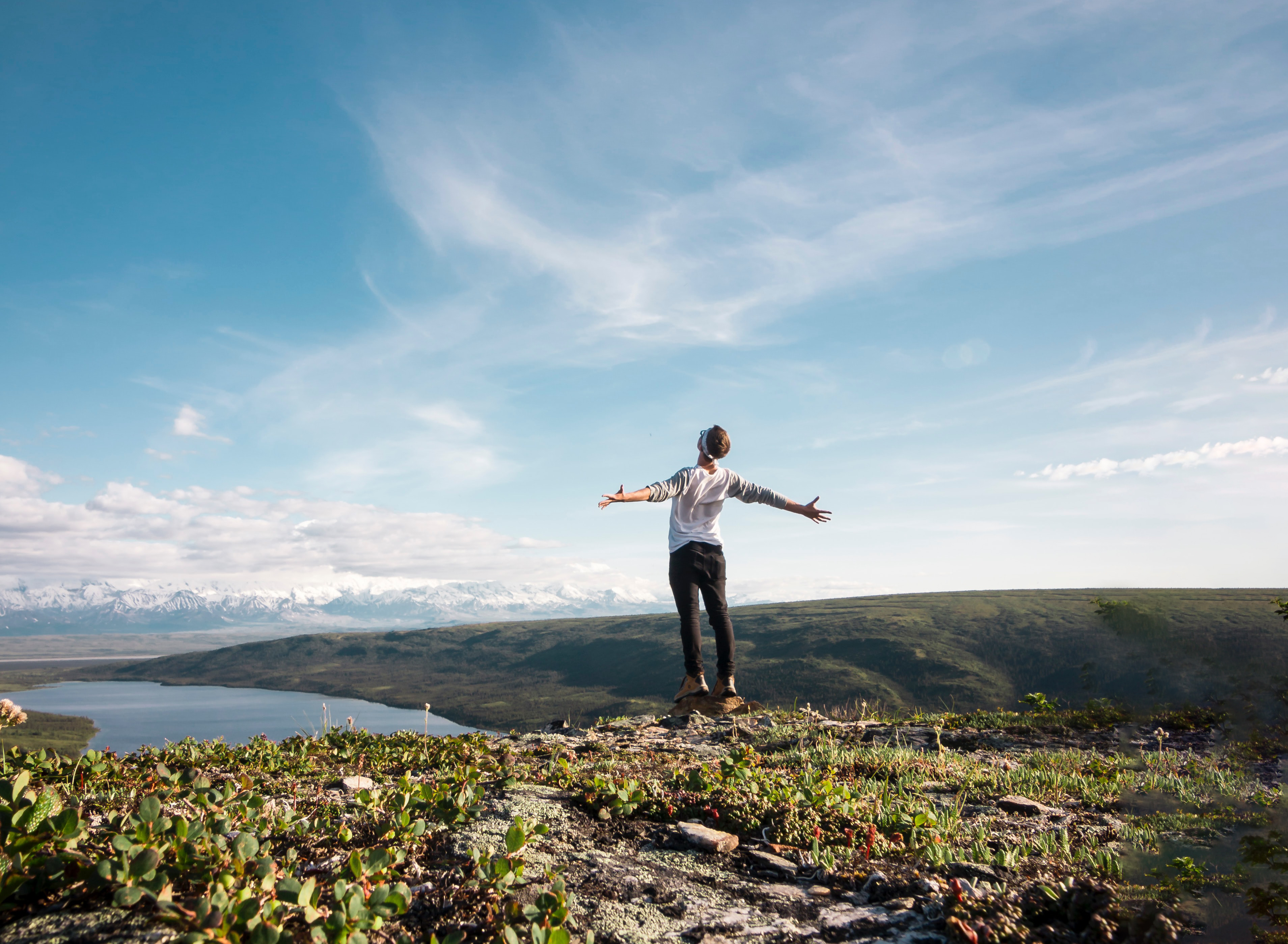 National Parks Trip —A hiker spreads arms as they face a magnificent vista.