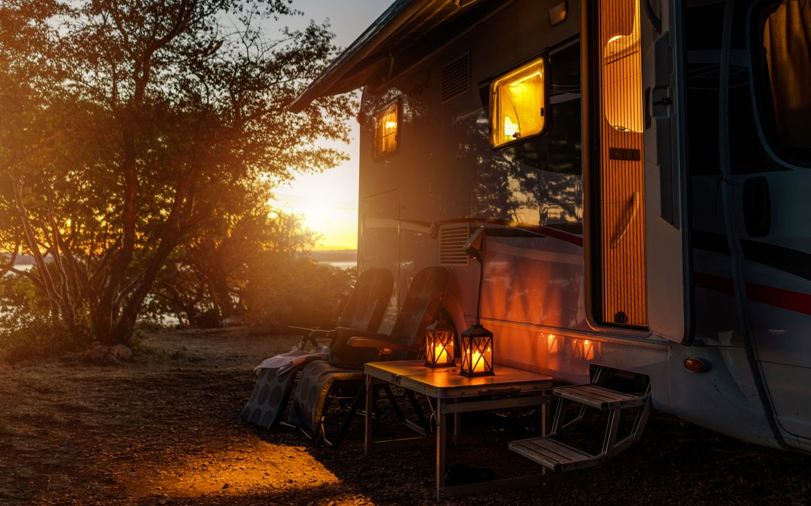 RV camper van camping warm night with outdoor chairs and romantic light from lanterns