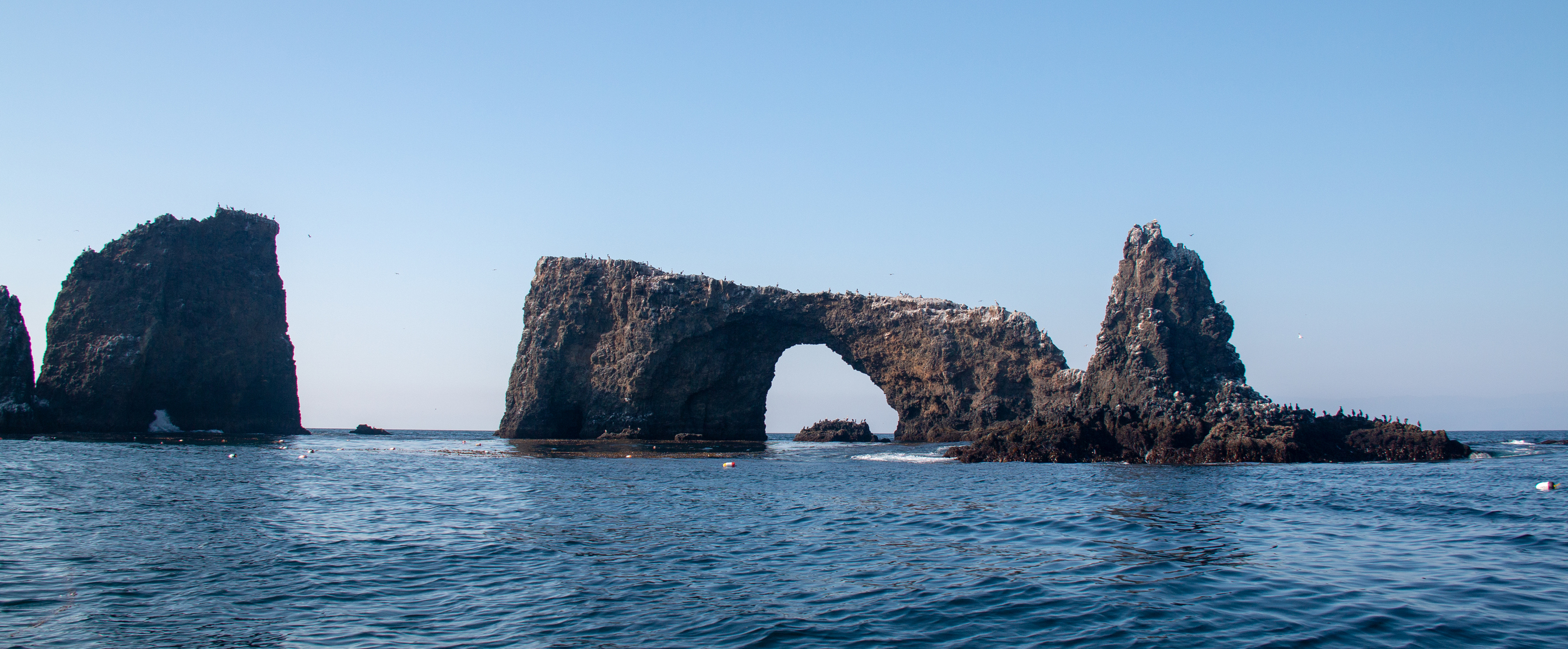 A rock arch and spire rise out of the ocean's surface.