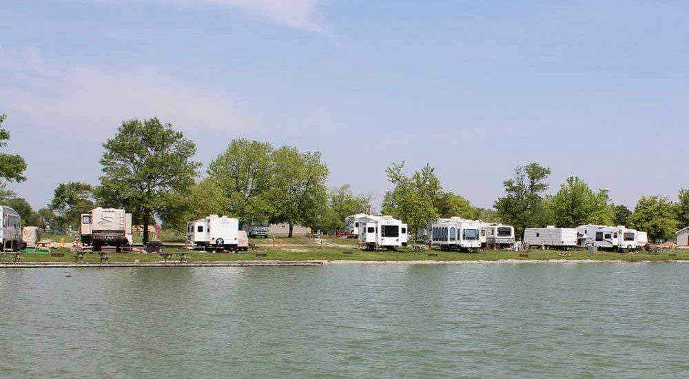 RVs camping along the banks of a wide river.