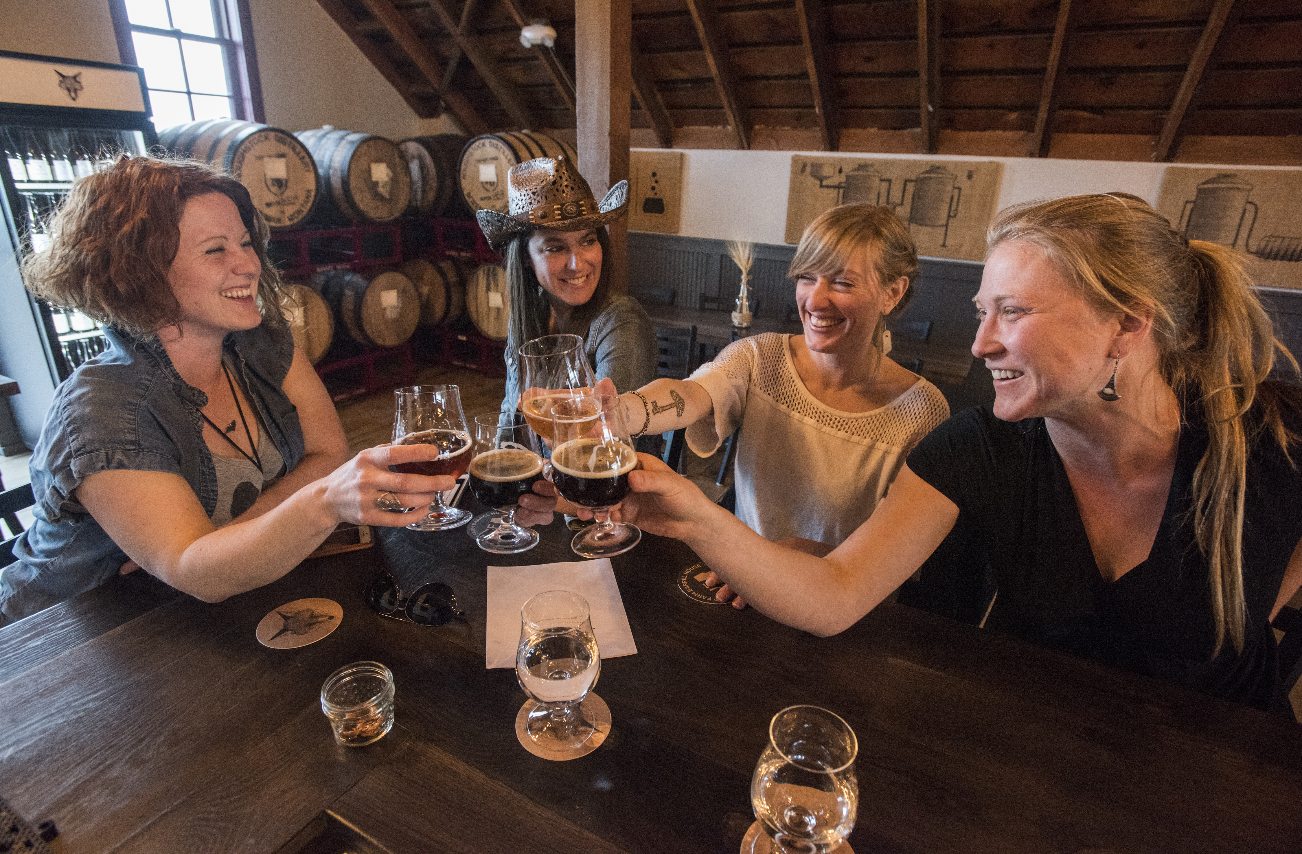 Four women clink their beer glasses in a jolly toast.