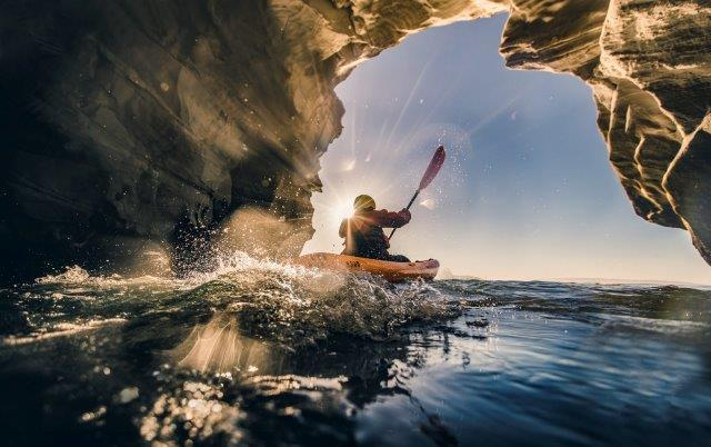 A kayaker paddles out of a cave and into the open ocean.