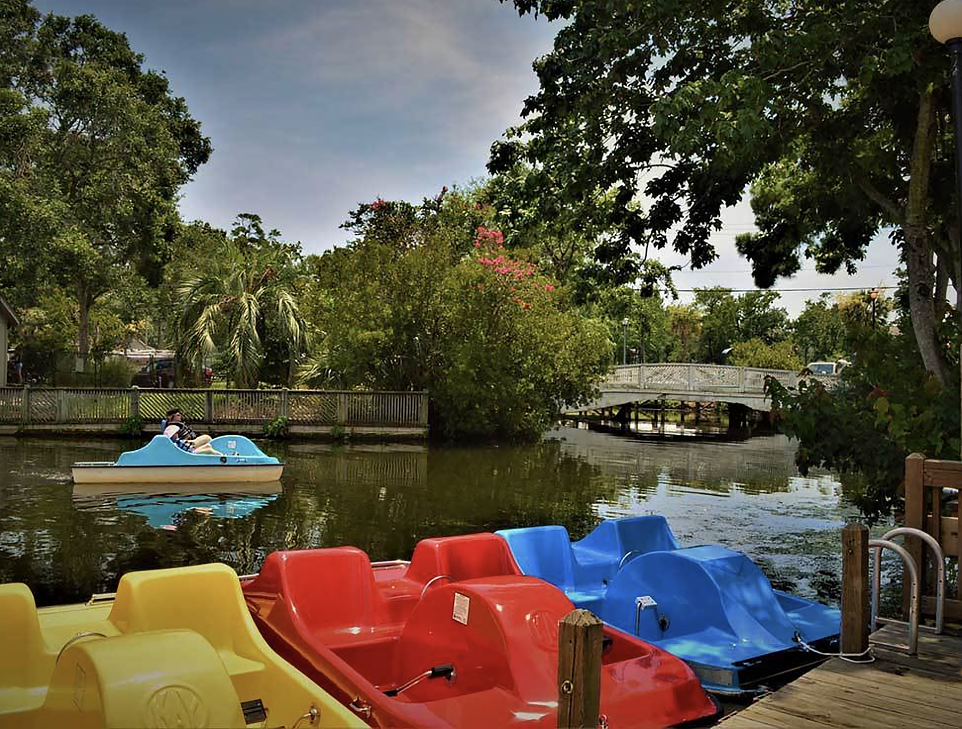 Woman pilots a pedal boat down a canal fringed with lush greenery.