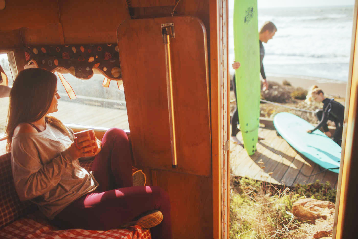 A woman sits in her RV and watches as her children wax surfboards.