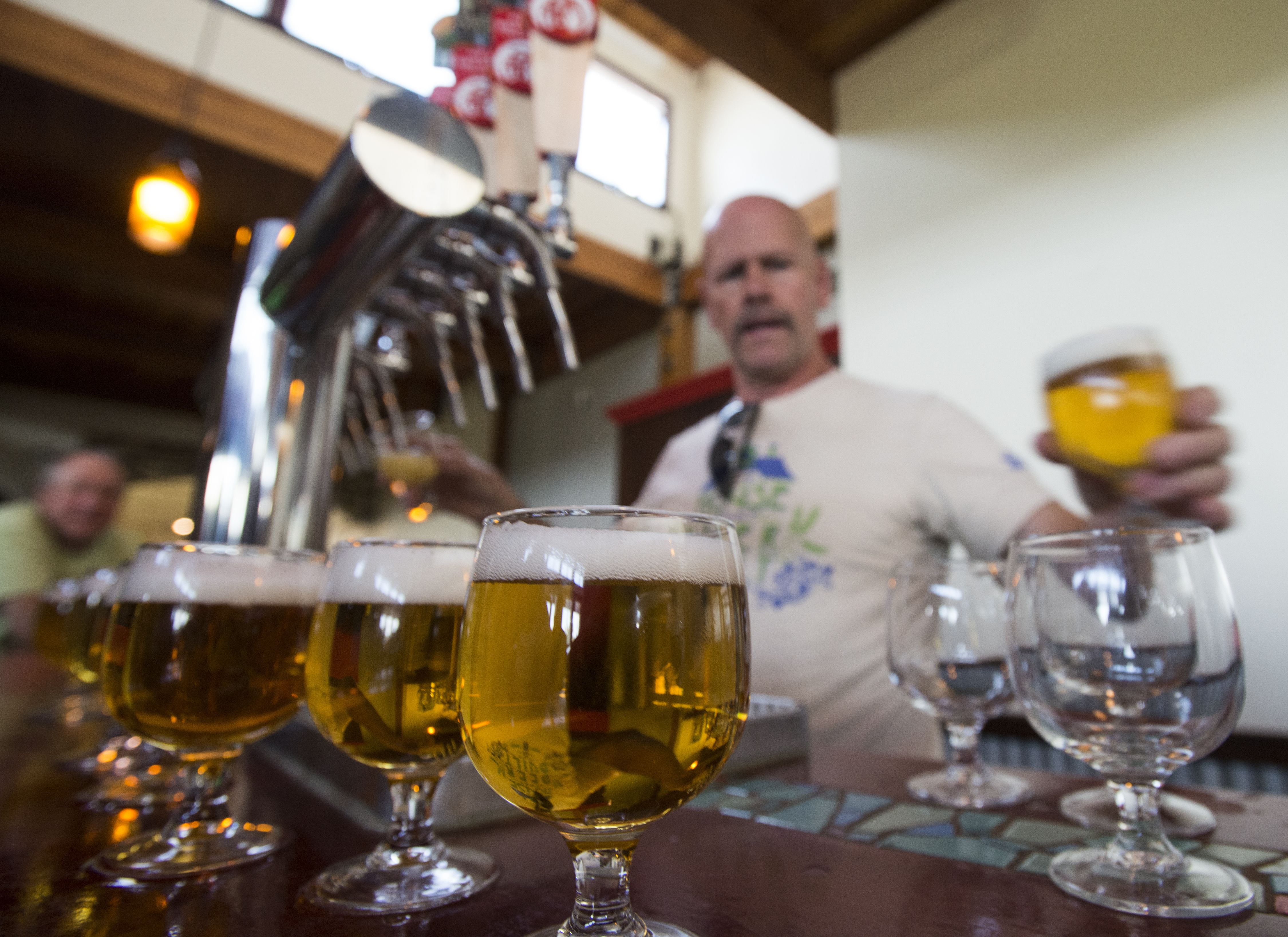 A man pours several amber beer glasses.