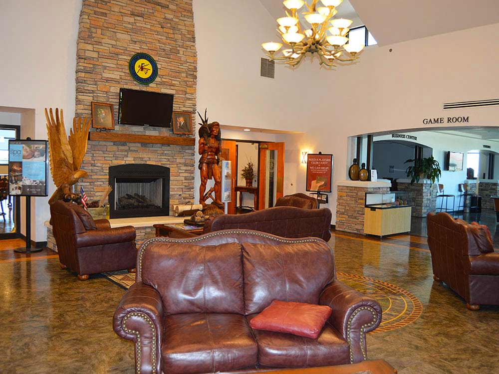A leather loveseat with fireplace in background.