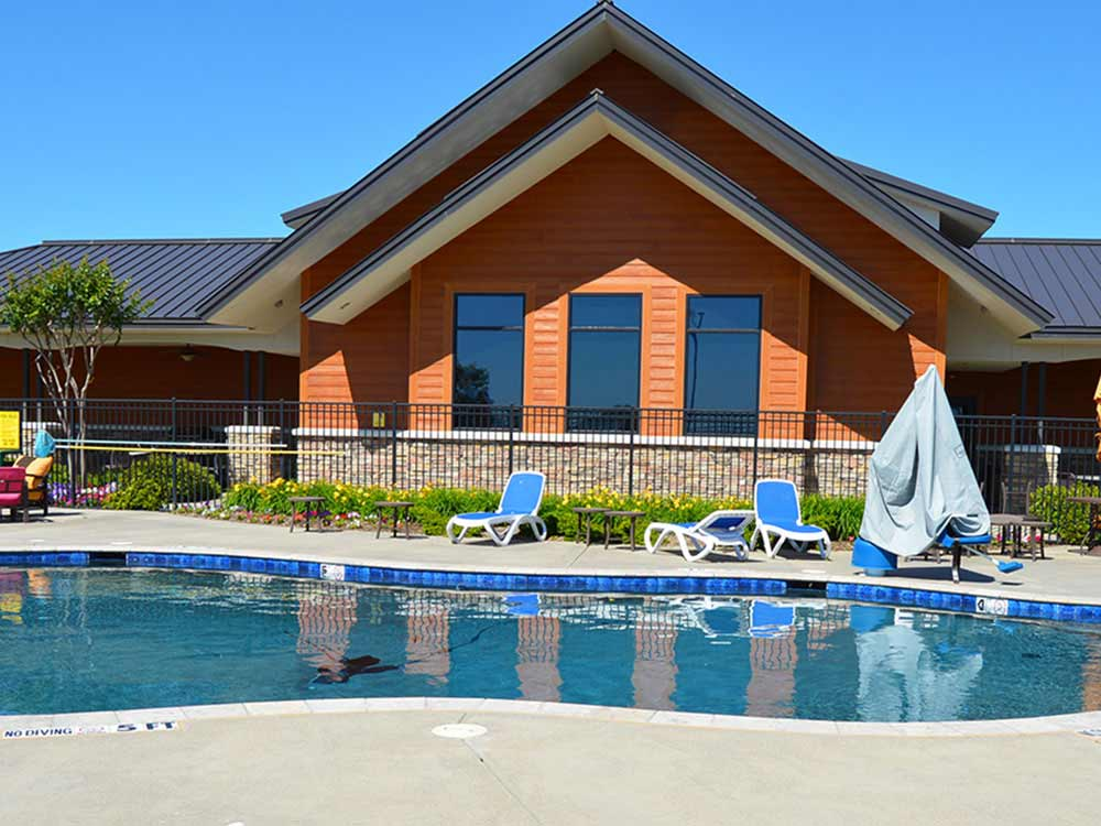 A swimming pool reflects a modern clubhouse.