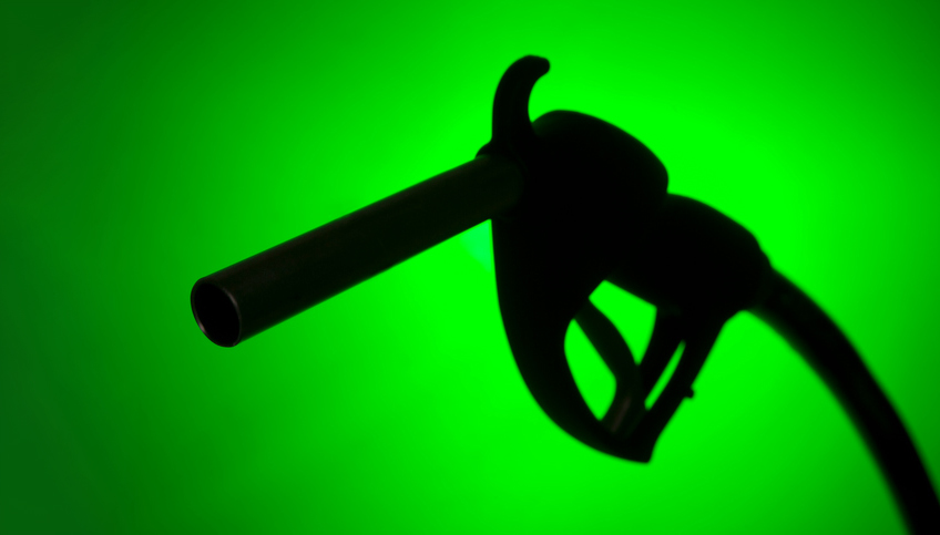 Silhouette of a gas pump against a green background.
