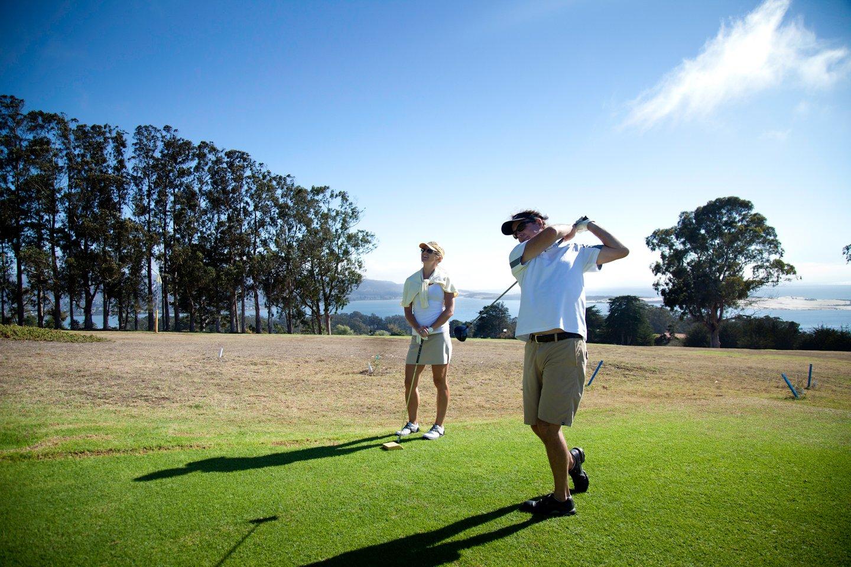 a man drives on a golf fairway while a woman watches.