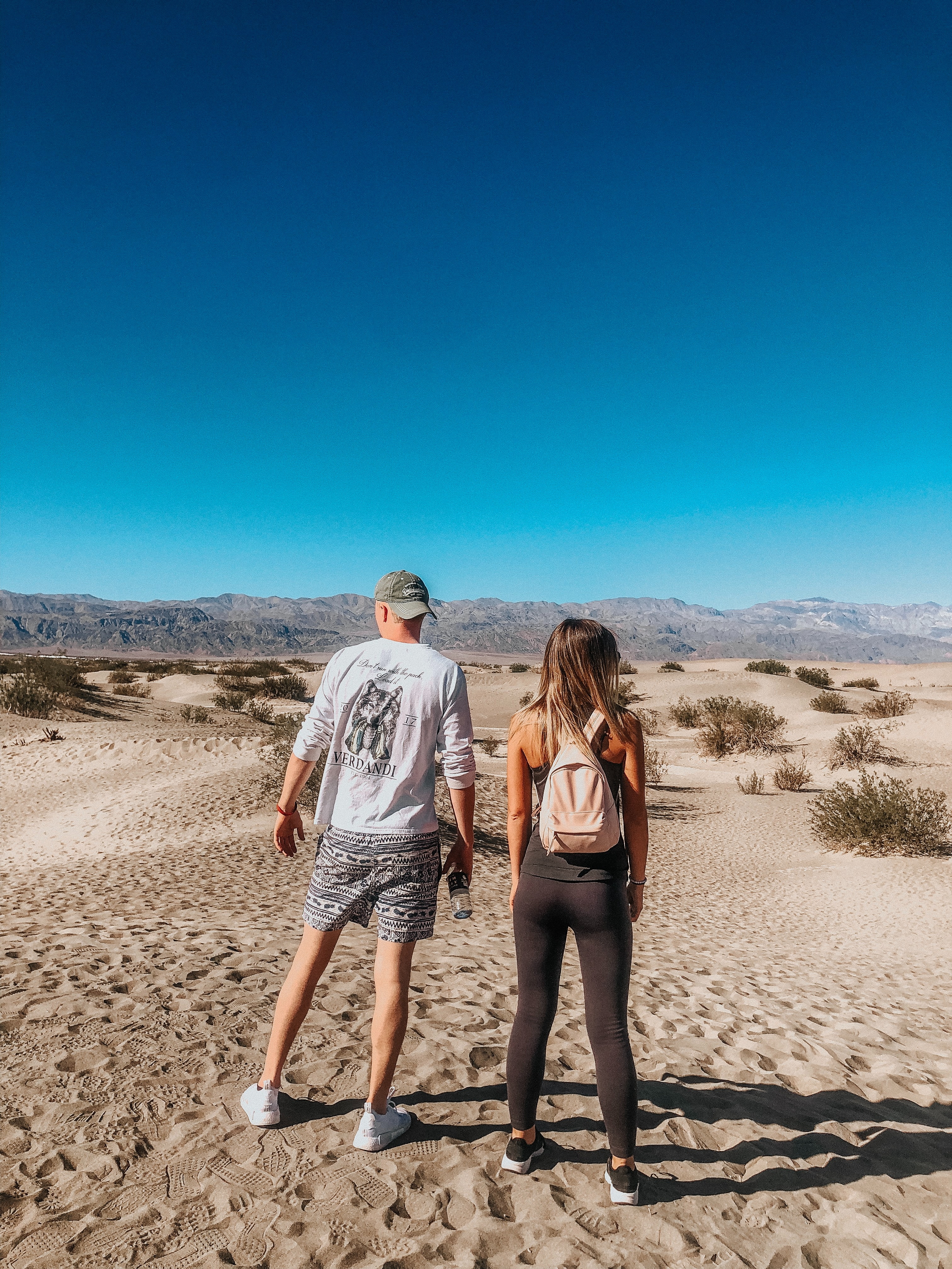Hikers on a sandy landscape evaluate the way ahead.