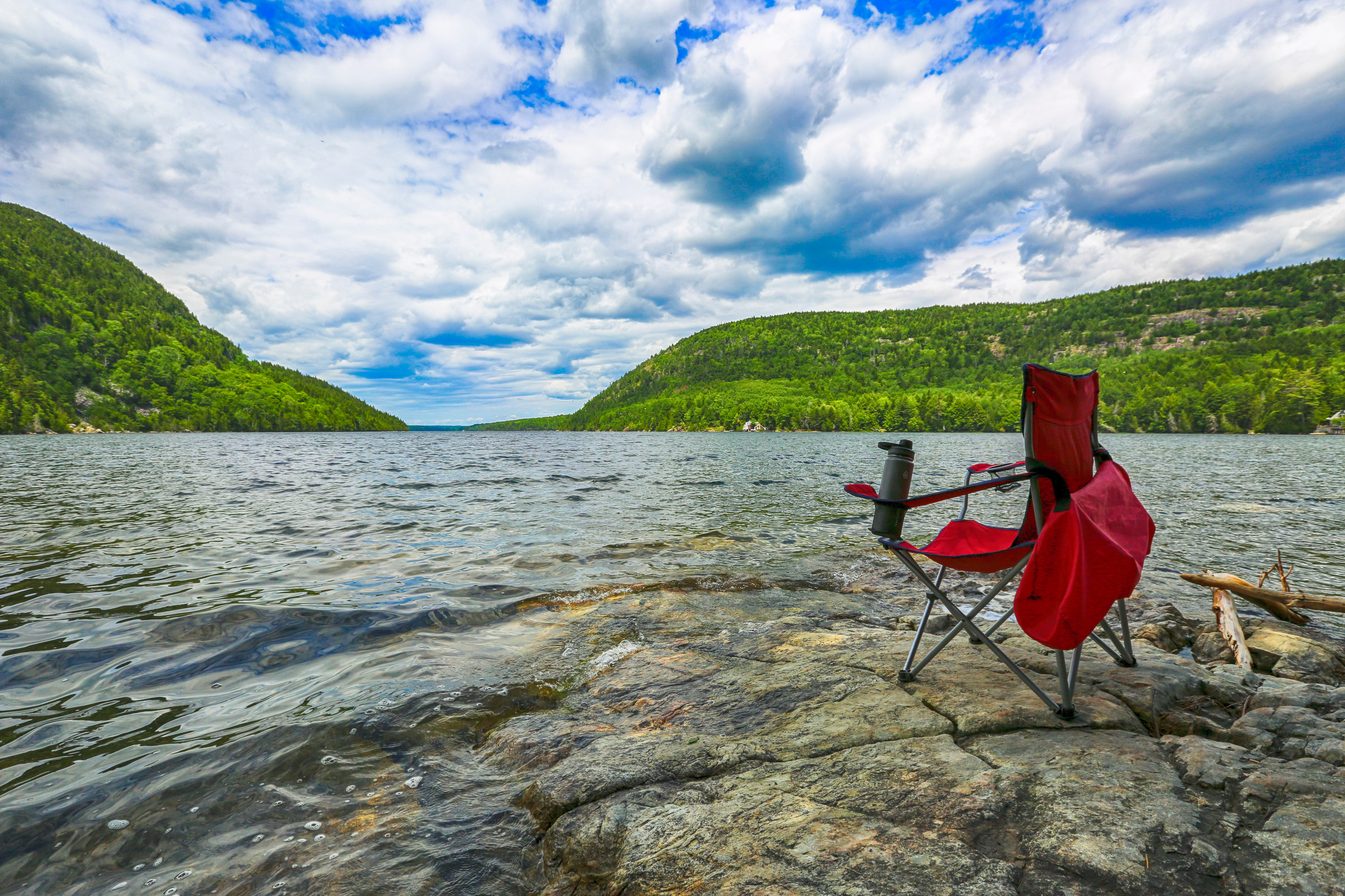 A red folding chair positioned in front of a lake.
