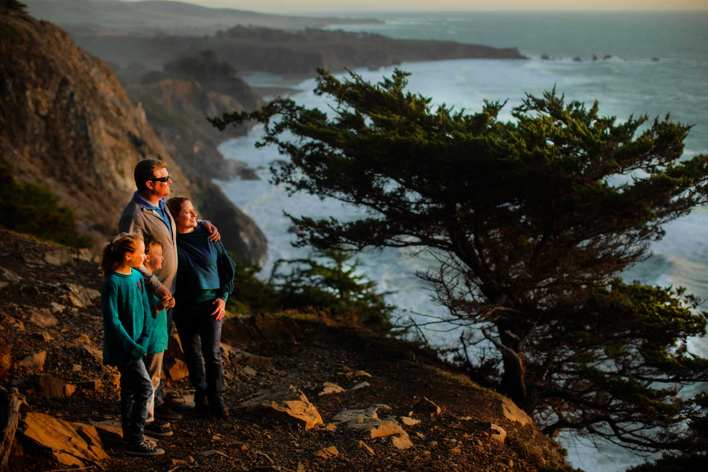 A family of four stand on a cliff and gaze out at the sunset.