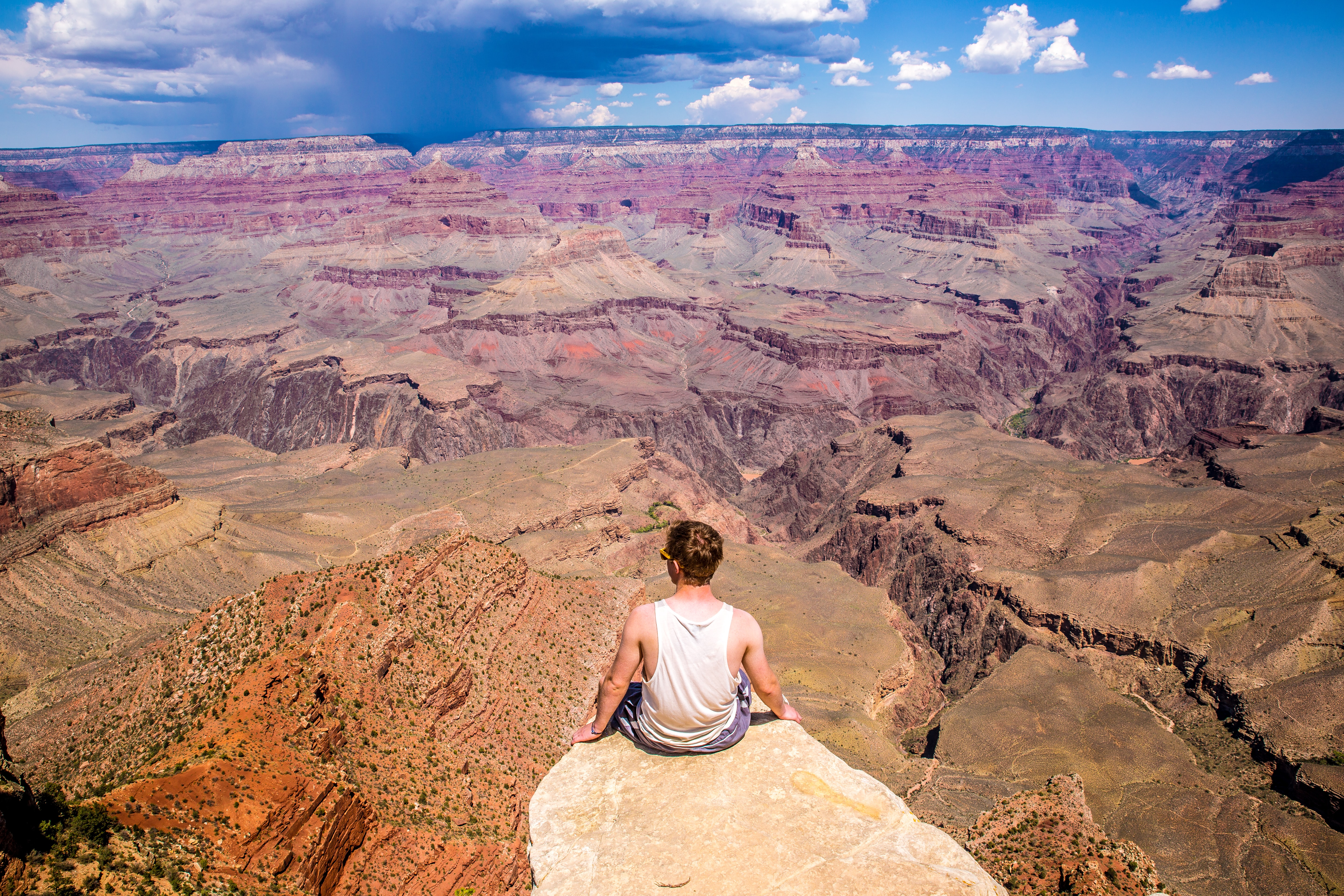 A lone visitor overlooks a vast canyon from a precipice.