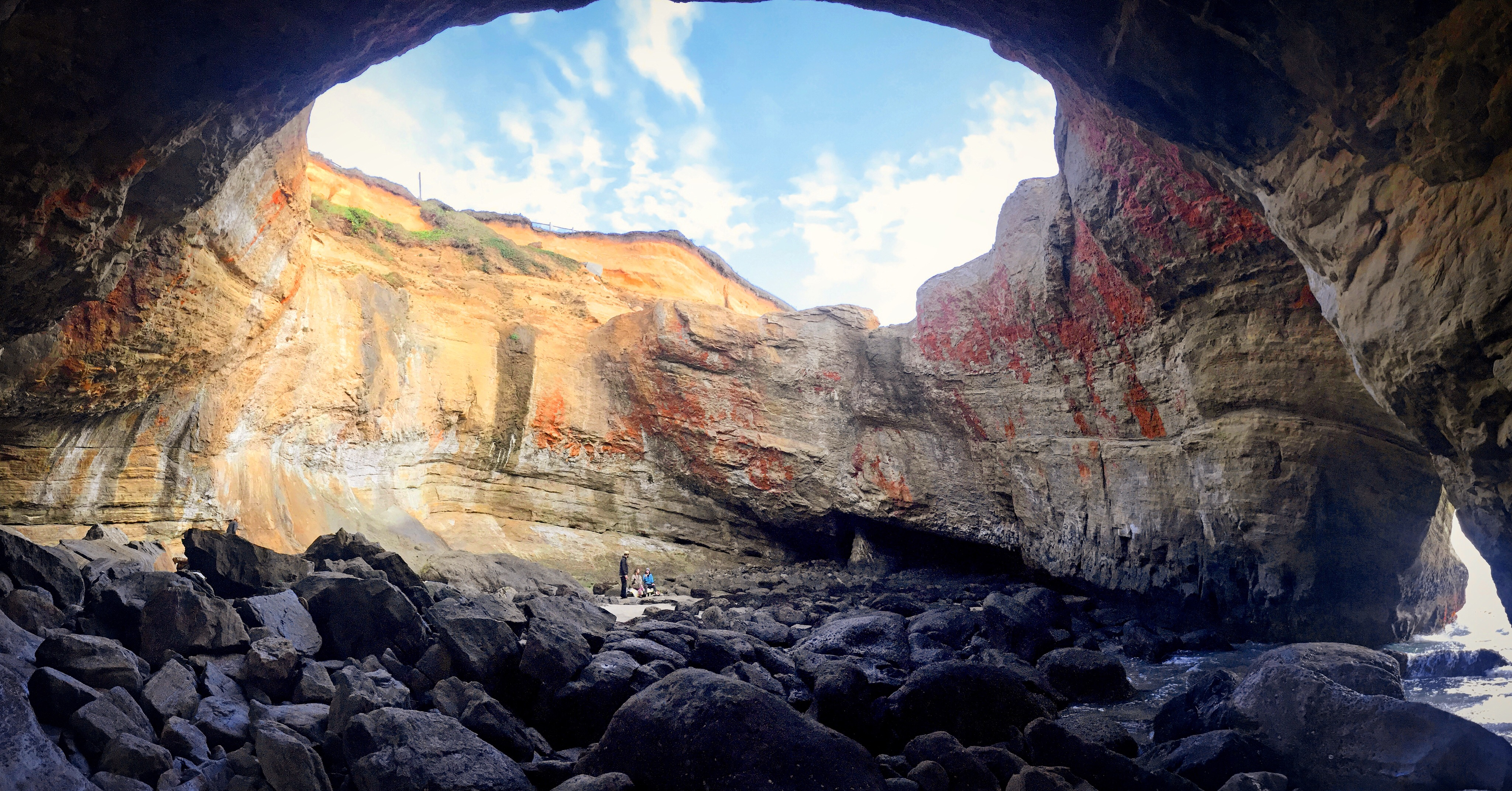 """View from the bottom of a vast rock """"bowl"""" near the ocean."""