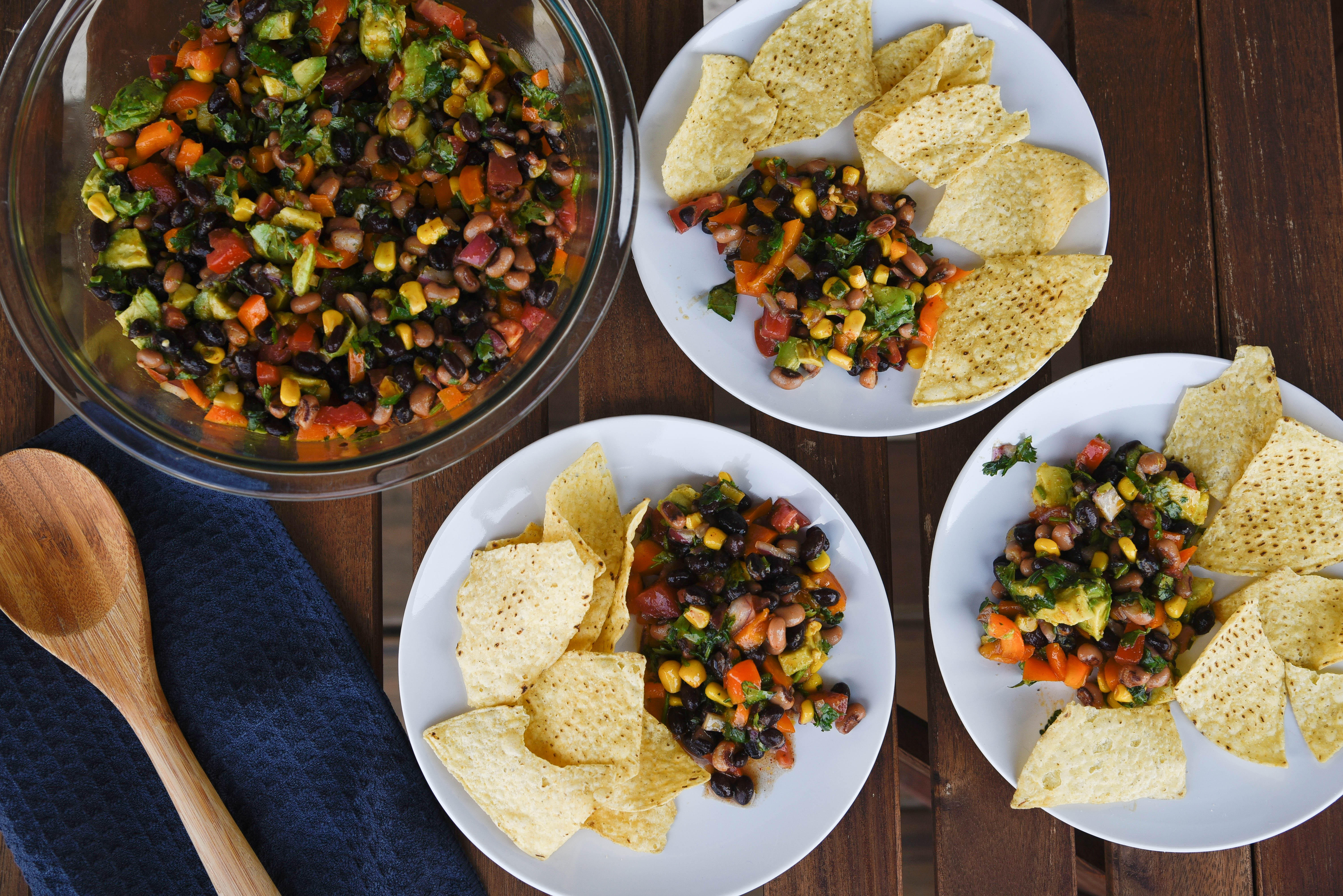 beans, black eyed peas, onion, tomatoes, corn, bell pepper, cilantro mixed together in bowl