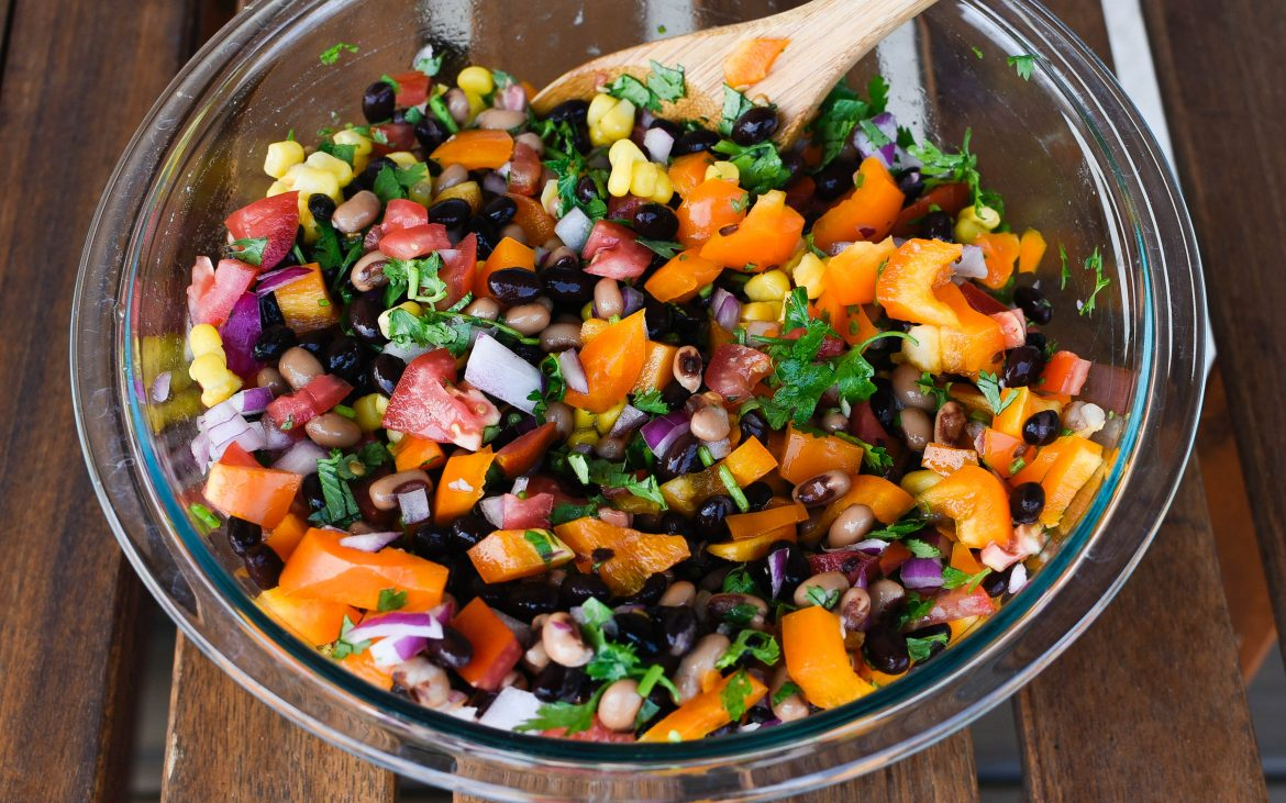 beans, black eyed peas, onion, tomatoes, corn, bell pepper, cilantro, and jalapeño in bowl