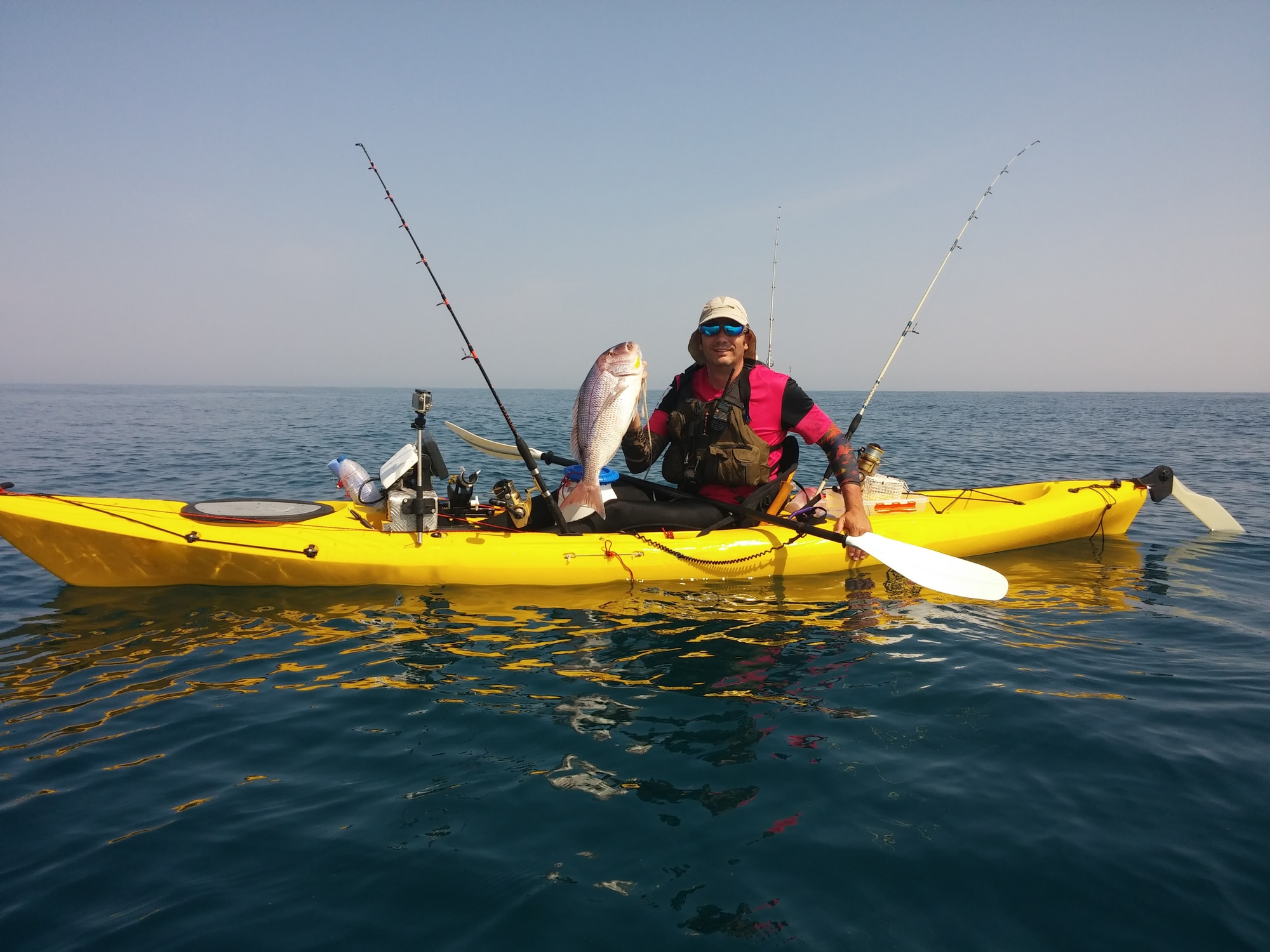 Guy in Yellow Kayak holds up a hefty Fish