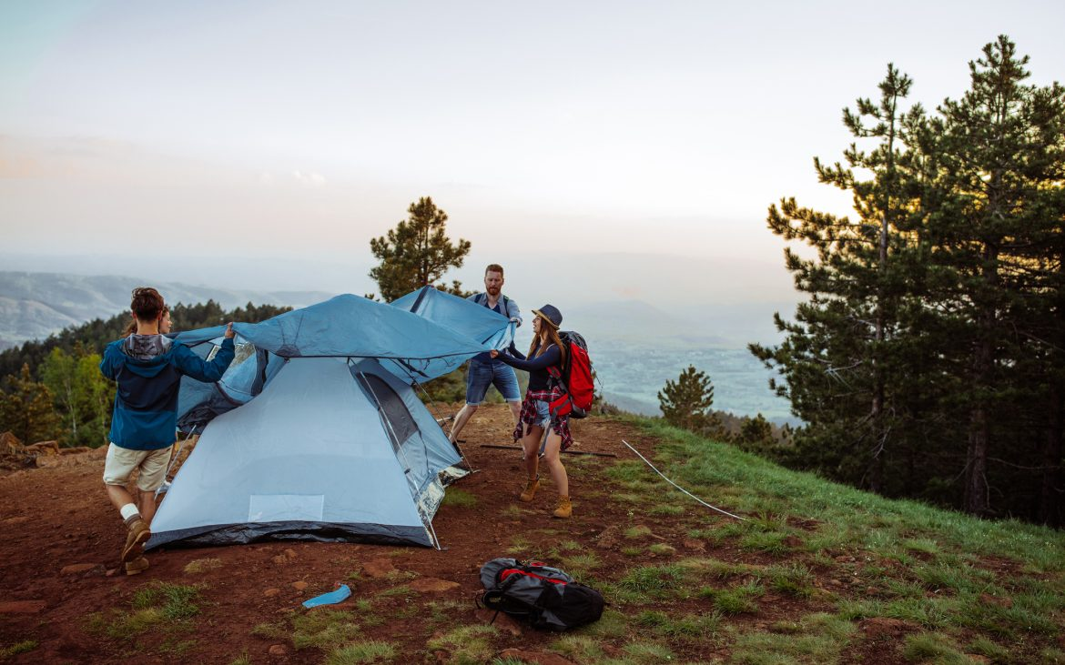 Shot of a group of friends setting up their tent while out hiking in the mountains.