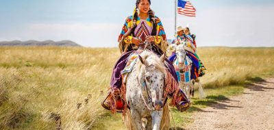 Nez Pierce of Lewis Clark Valley —A woman in tribal dress rides a white horse on a trail.