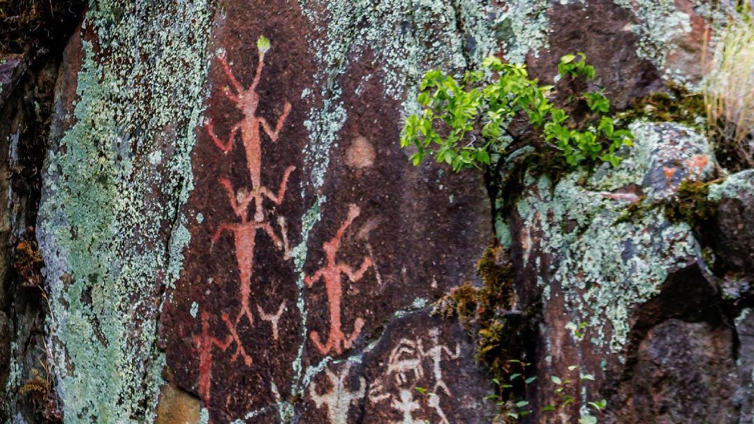 Petroglyphs adorn a sheer rock face.