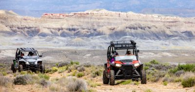 A pair of ATVs speeding across rugged countryside.