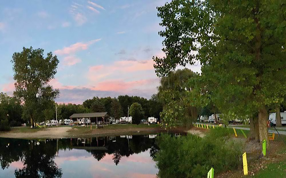 Scenic RV campground reflected on the surface of a placid lake.